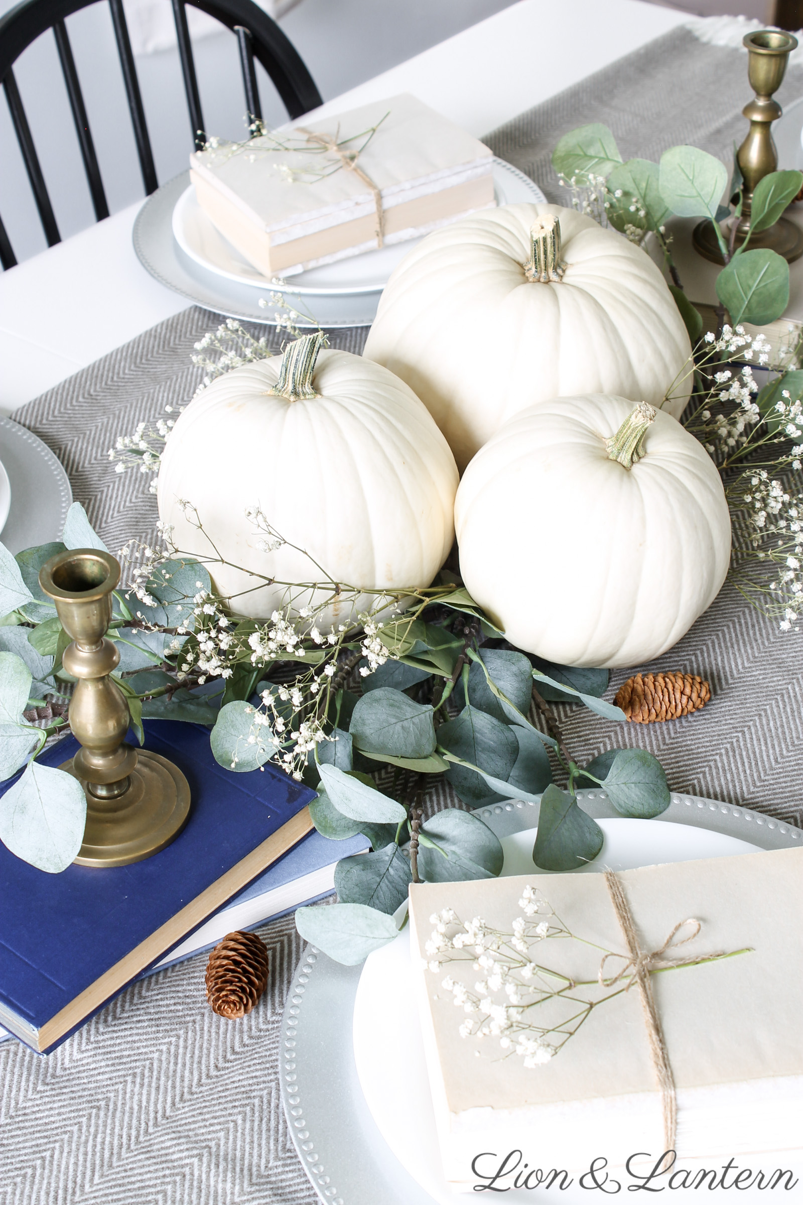 Thanksgiving Tablescape at LionAndLantern.com. Farmhouse Thanksgiving, Thanksgiving table decor, holiday decor, neutral, budget, eucalyptus, white pumpkins, book bundles, black chairs, white table.