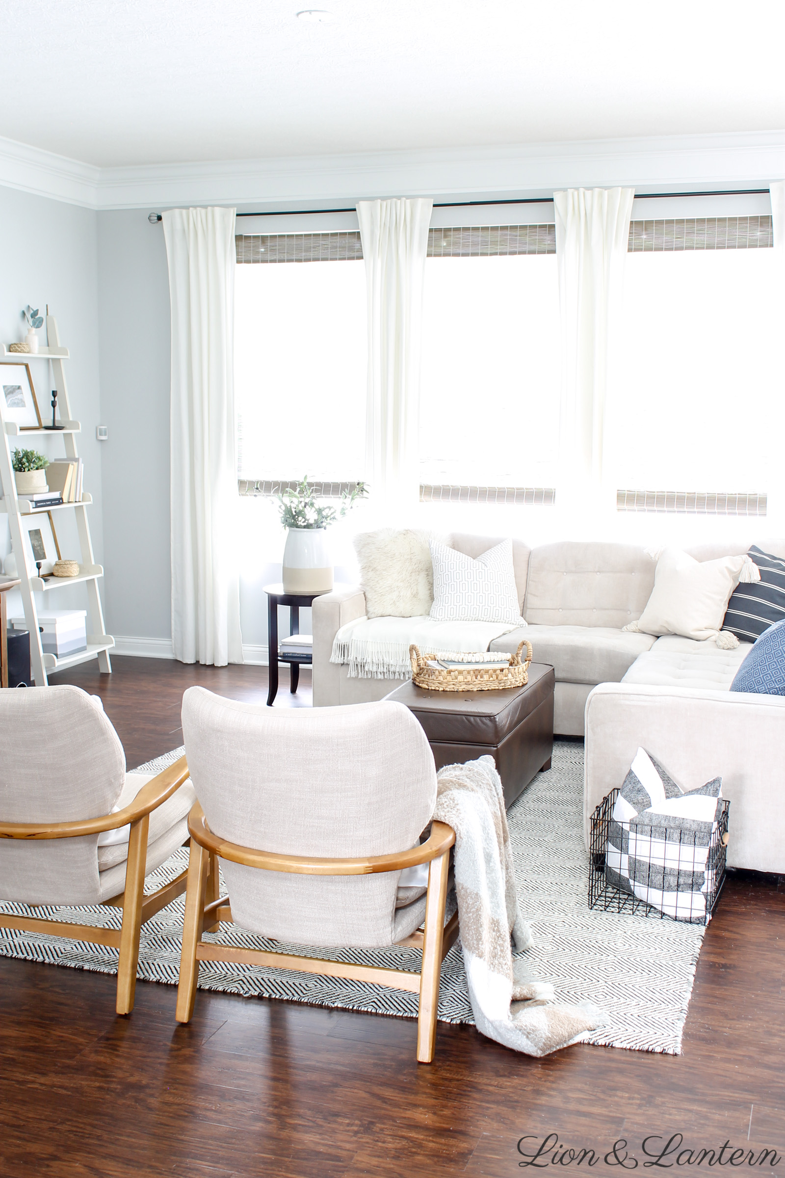 Cozy Coastal Living Room at LionAndLantern.com | coastal farmhouse, neutral living room, bright and airy, cream sofa, ladder shelf, budget decor, modern wood accent chair, modern farmhouse