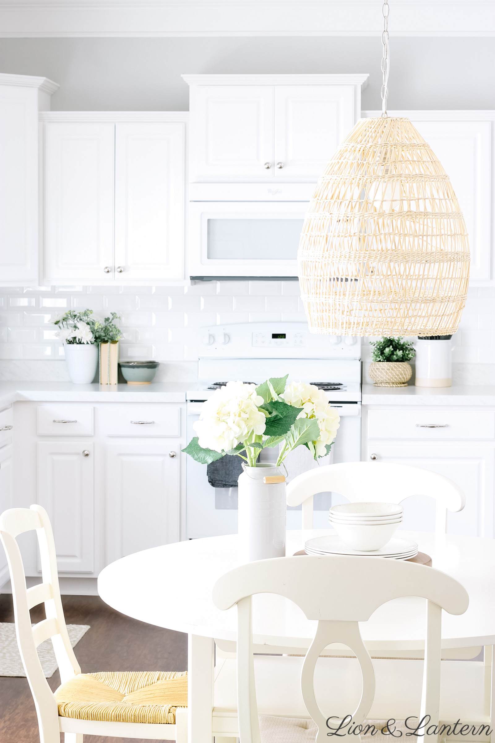 Spring Home Tour 2019 at LionAndLantern.com | vintage kitchen decor, round white dining table, woven pendant, white subway tile, budget decorating, neutral kitchen