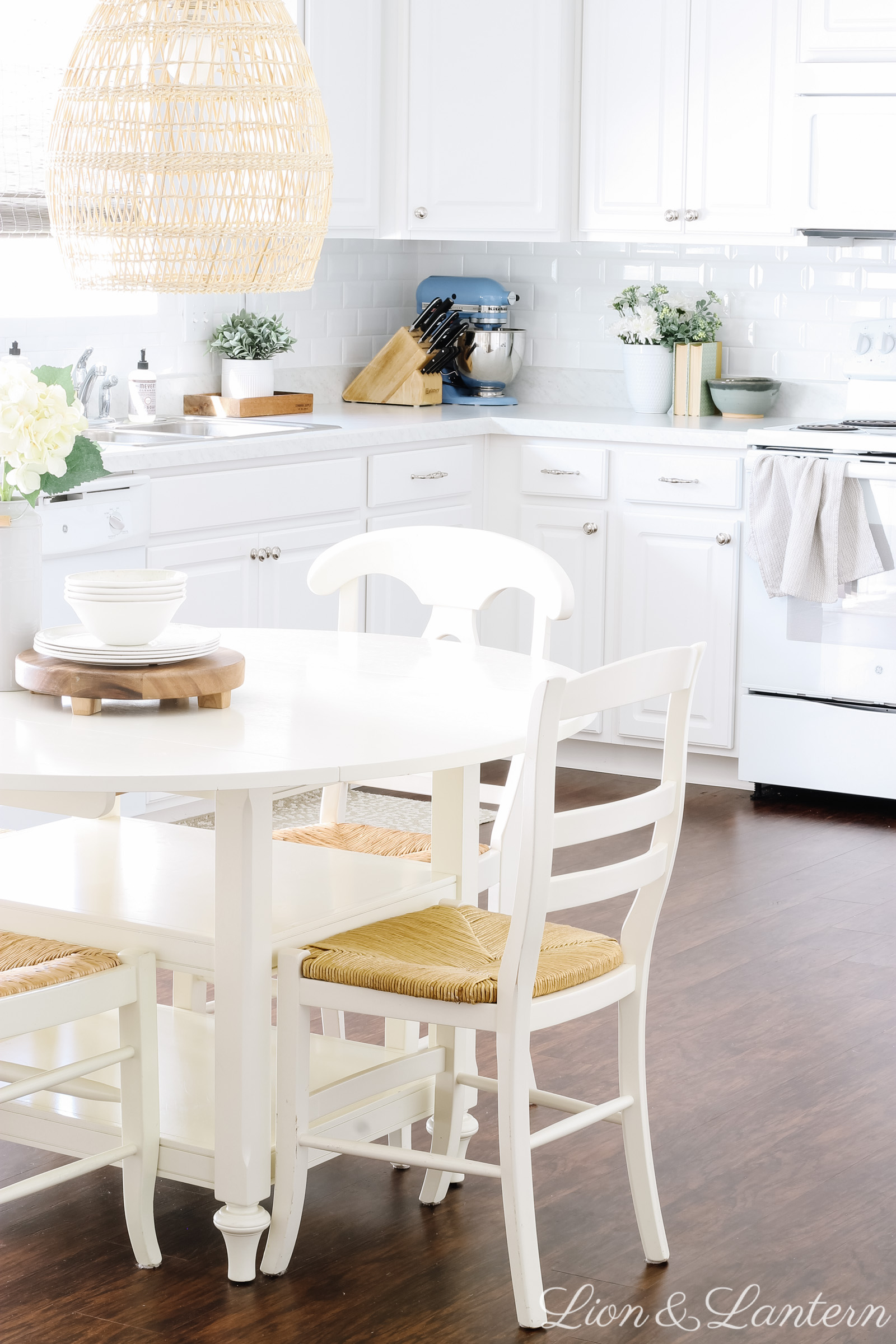 White Kitchen Tips: Adding Character on a Budget at LionAndLantern.com | vintage kitchen decor, round white dining table, woven pendant, white subway tile, budget decorating, neutral kitchen