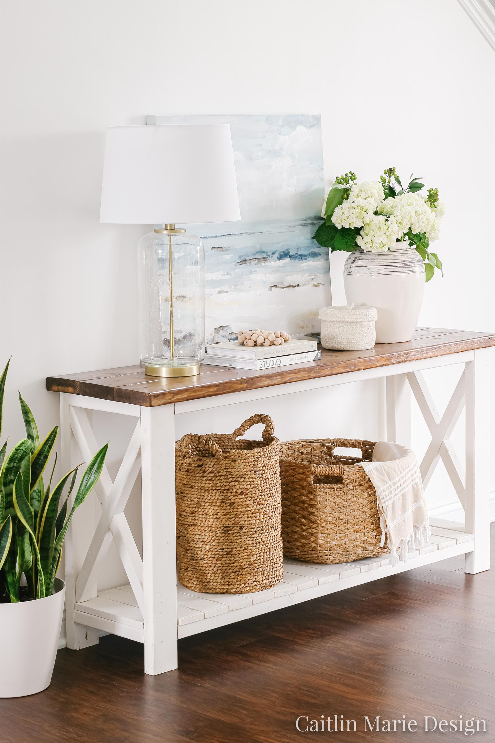 Summer Home Tour 2019 | coastal entryway decor, pottery vase, white hydrangeas, bead garland, rattan baskets, ocean painting