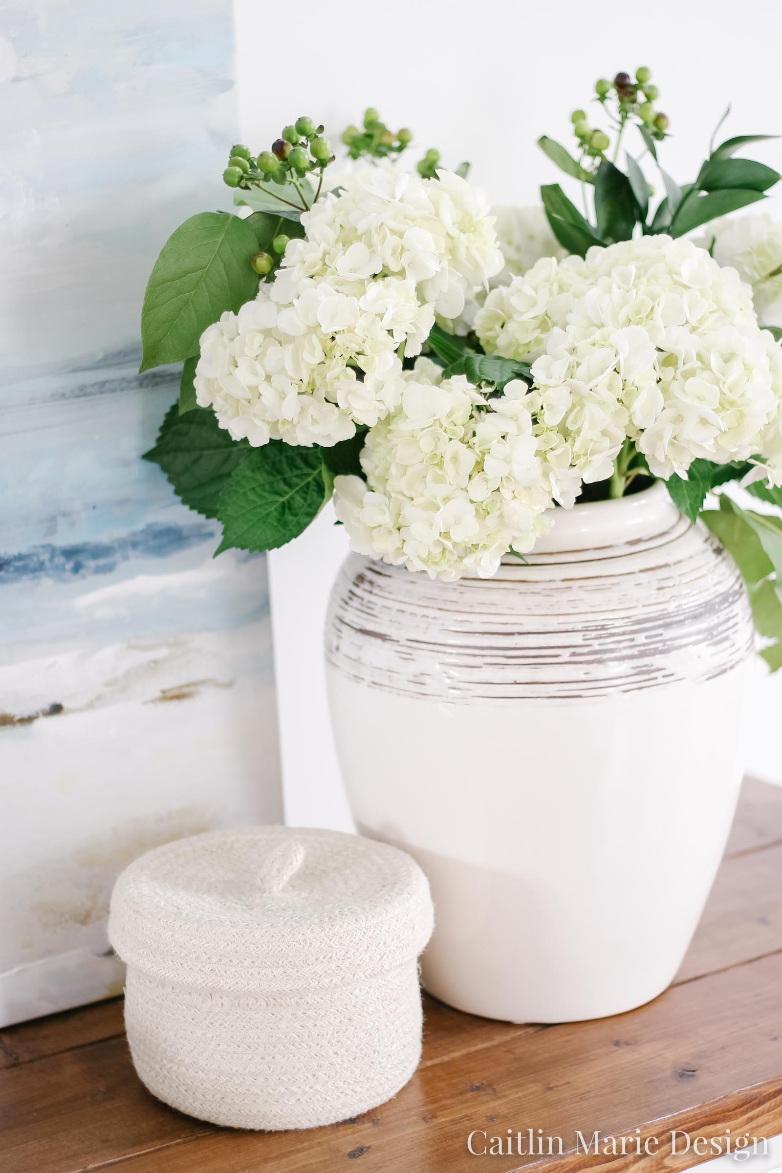 Summer Home Tour 2019 | coastal entryway decor, pottery vase, white hydrangeas, bead garland, rattan baskets, ocean painting