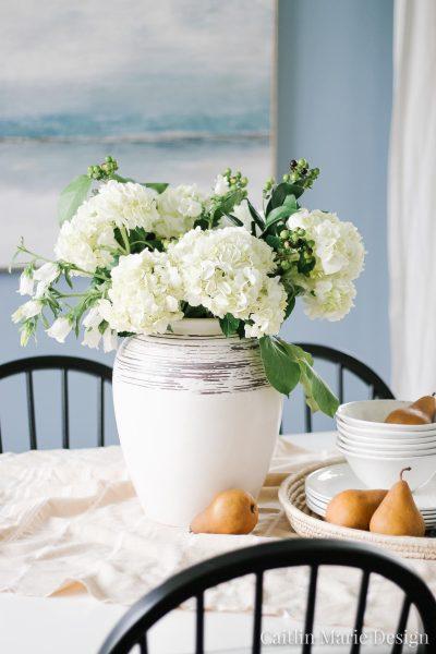 Simple Summer Tablescape | hydrangeas, pears, coastal farmhouse, blue dining room, minimalist abstract art, black dining chairs