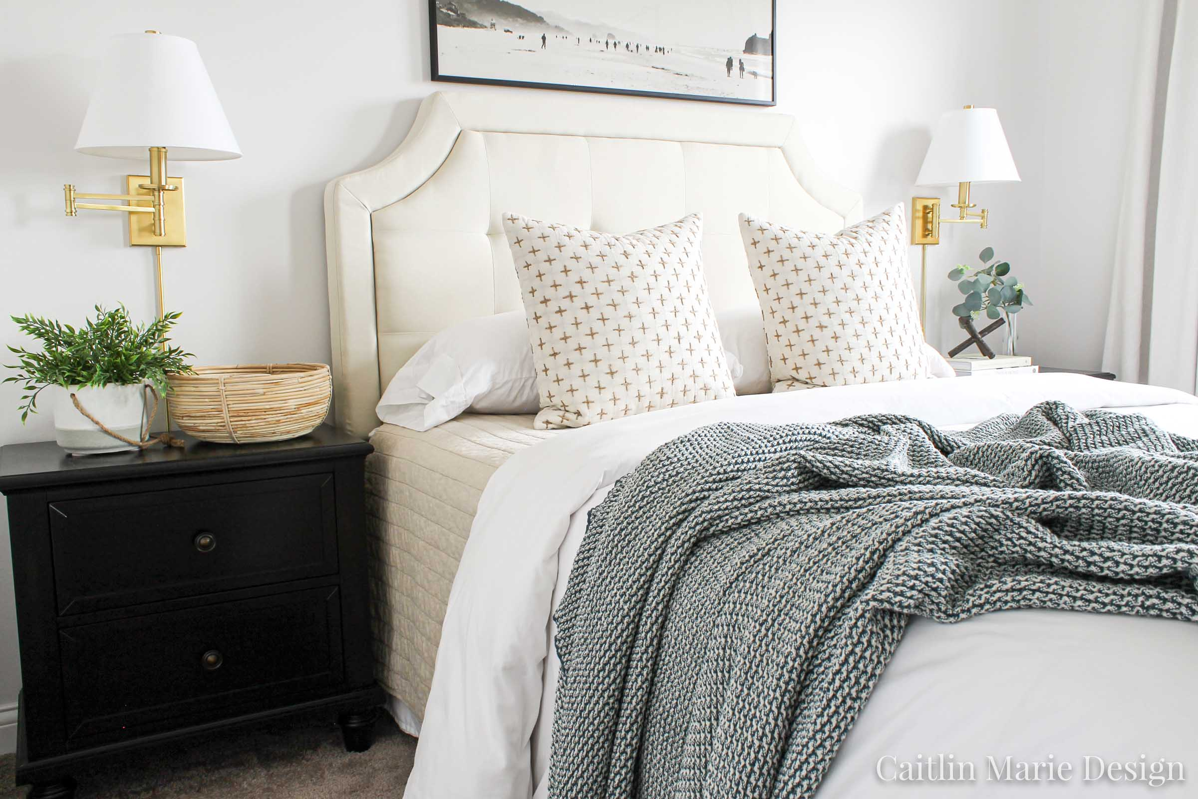 Spring Bedroom Decor | Loloi Layla rug, brass wall sconces, wide art above the bed, tufted headboard, dark wood nightstand