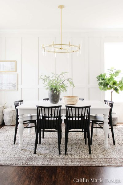 Coastal Dining Room Reveal | One Room Challenge Spring 2020, white farmhouse table, black Windsor dining chairs, brown vintage rug, brass modern chandelier, coastal landscape artwork, budget decor, coastal decor