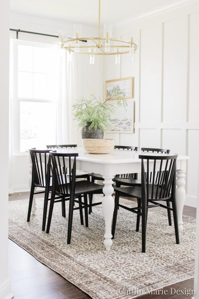 Black Dining Chair Update with Article | coastal modern dining room, brown vintage rug, landscape art, aged stone vase, board and batten accent wall
