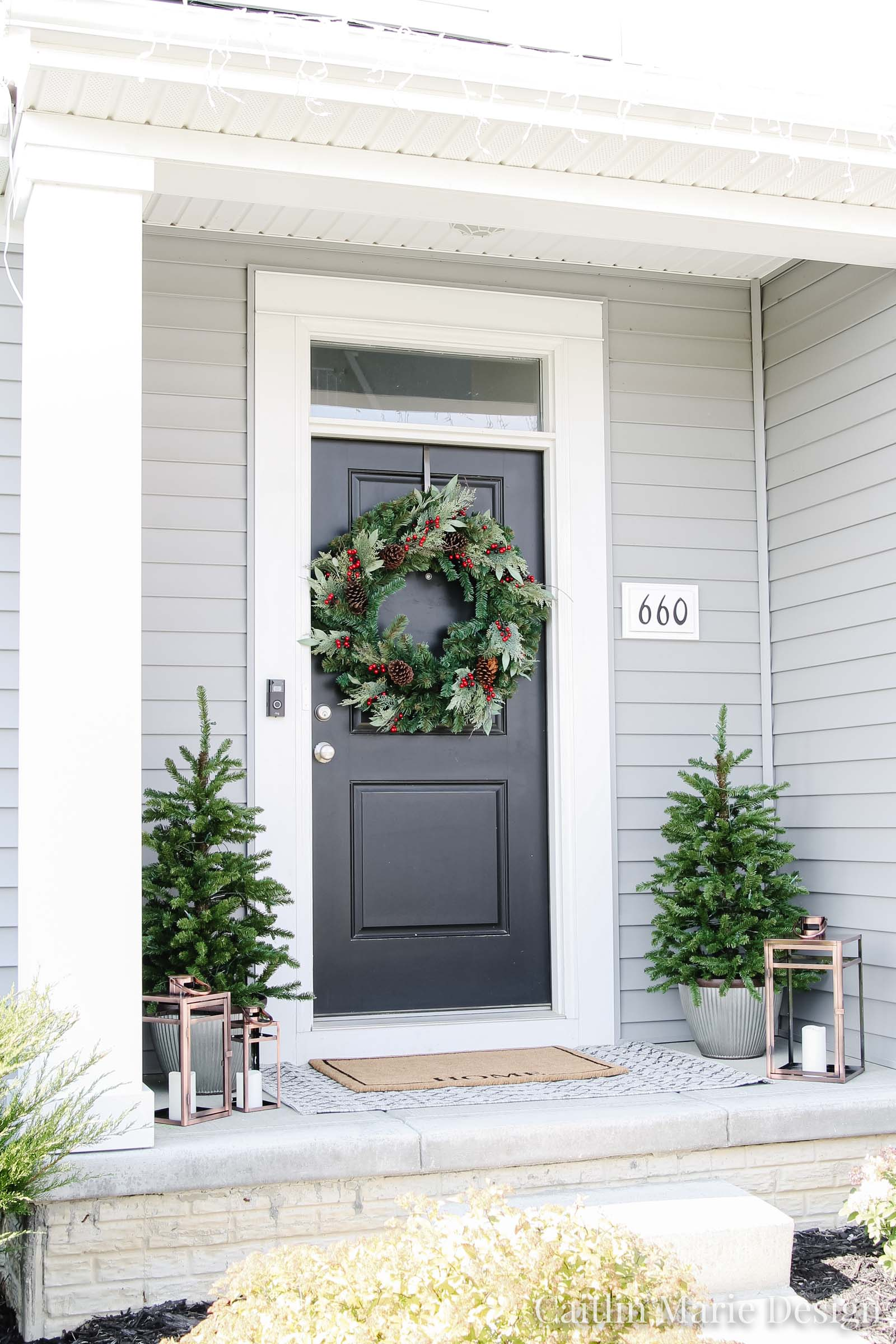 Holiday Front Porch Reveal - The Home Depot Style Challenge | black front door, large mixed pine wreath, small artificial Christmas trees, galvanized planters, welcome mat