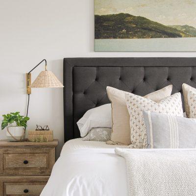 coastal modern master bedroom with rattan sconce, vintage artwork, layered bedding