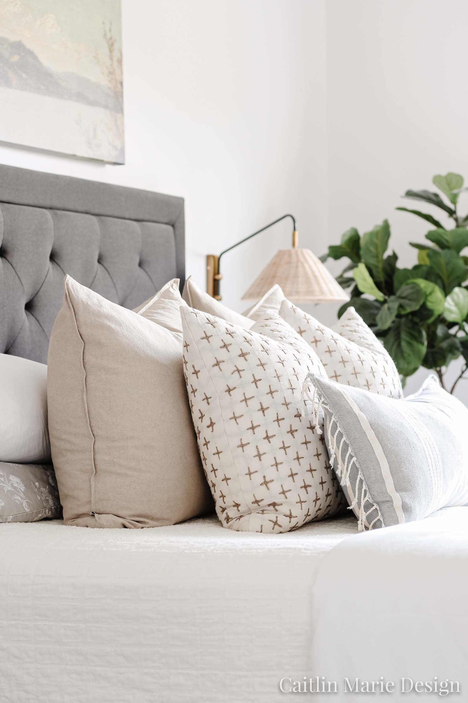 Coastal master bedroom layered throw pillows, rattan sconce, black upholstered headboard