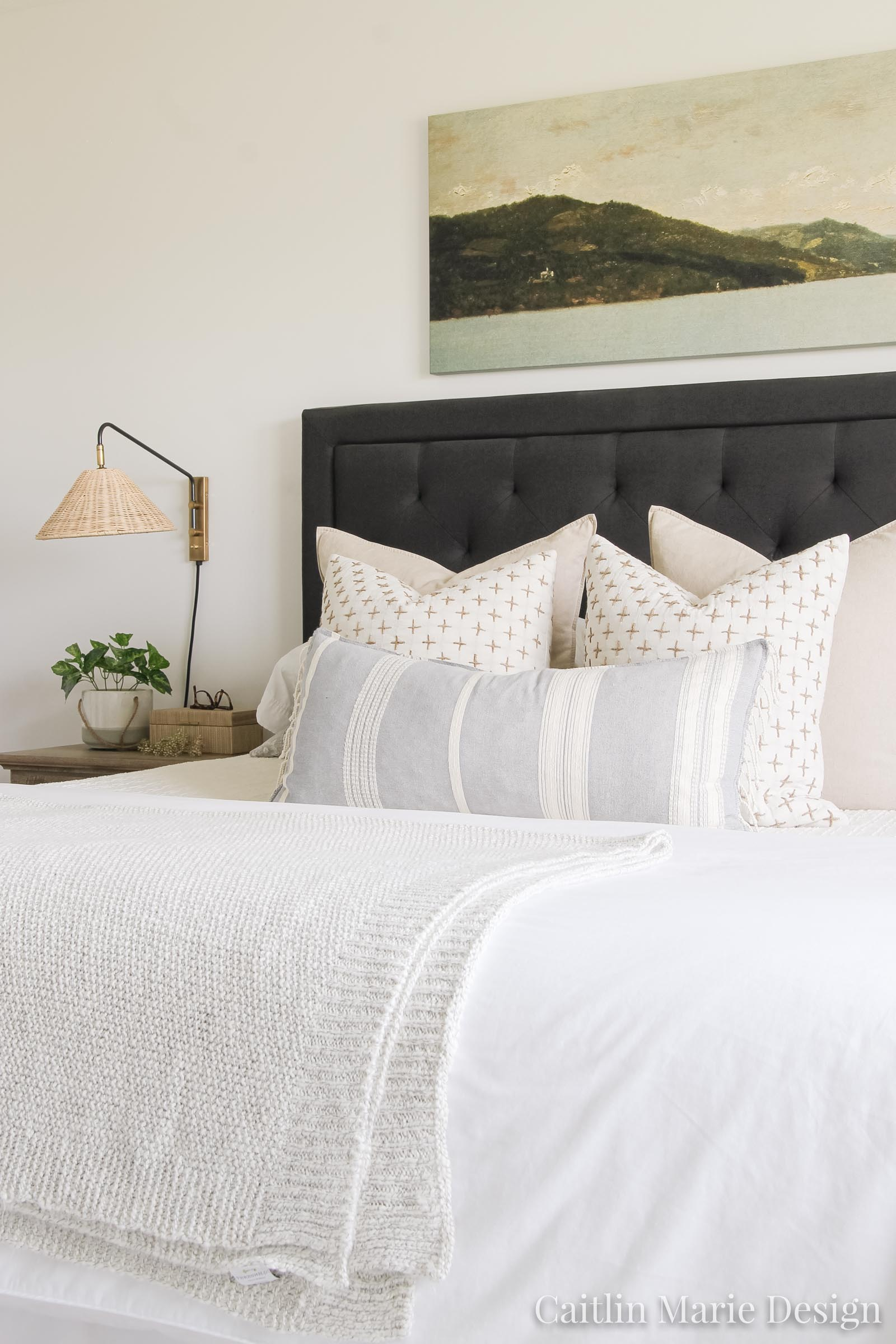 Coastal master bedroom, layered bed pillows, long lumbar, rattan sconce, sweater throw blanket, modern coastal decor