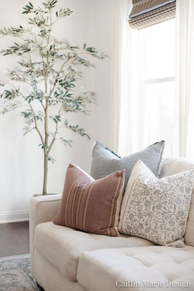 Spring Throw Pillows that Actually Work for Any Season | artificial olive tree, throw pillow combination, cream sofa