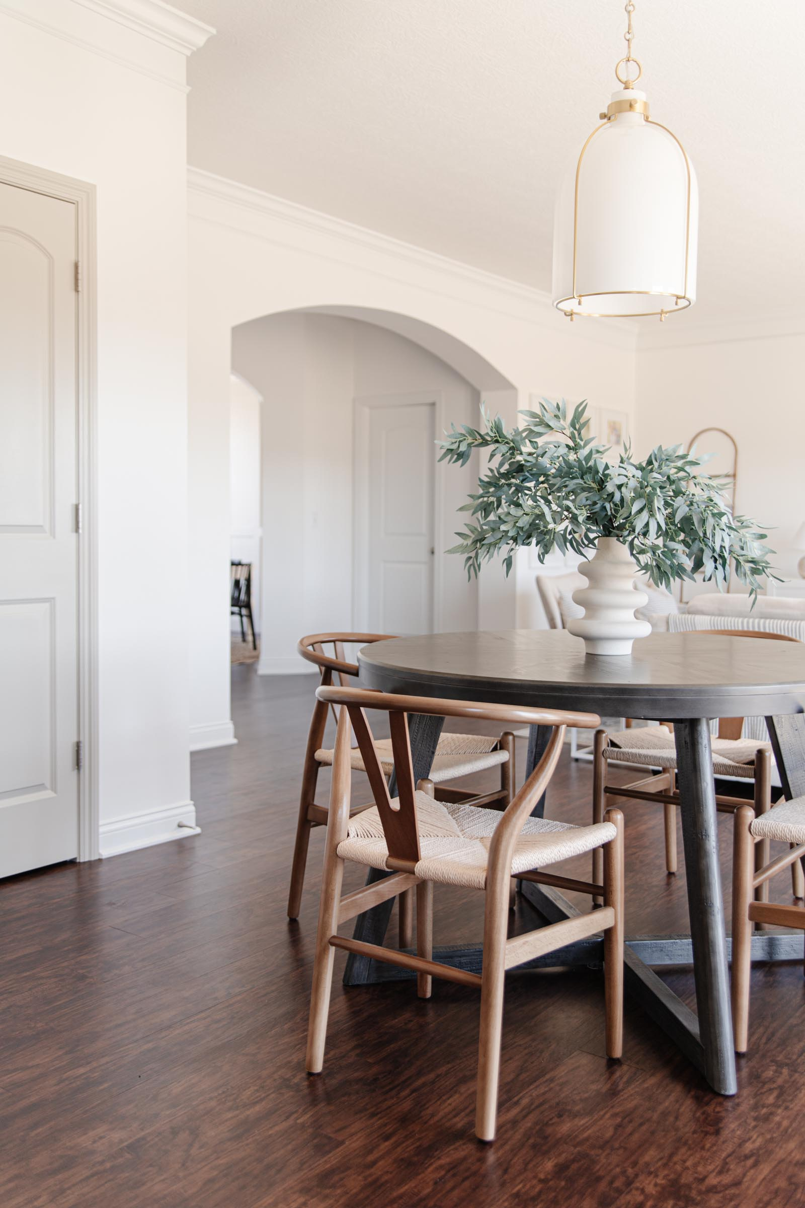 round breakfast table, wishbone chairs, brass pendant light, faux greenery