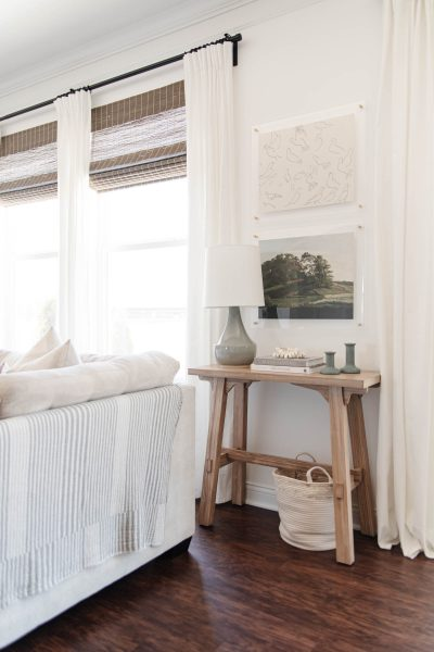 Tips for Styling an Awkward Space in Your Home | small console table, framed stacked artwork with acrylic frames, white curtains