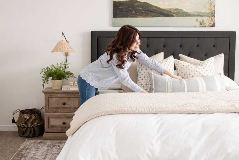 modern coastal bedroom, landscape painting, layered bedding, making the bed