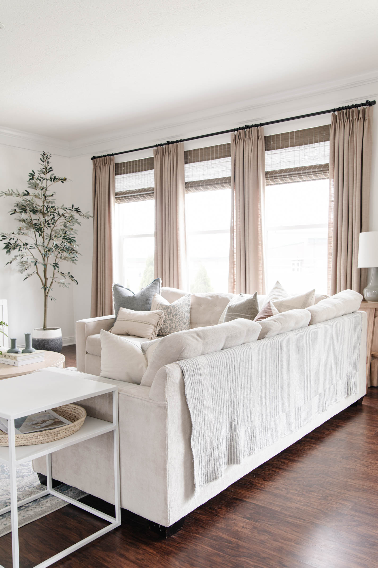 living room with gray beige pinch pleat drapes, cream sofa, artificial olive tree