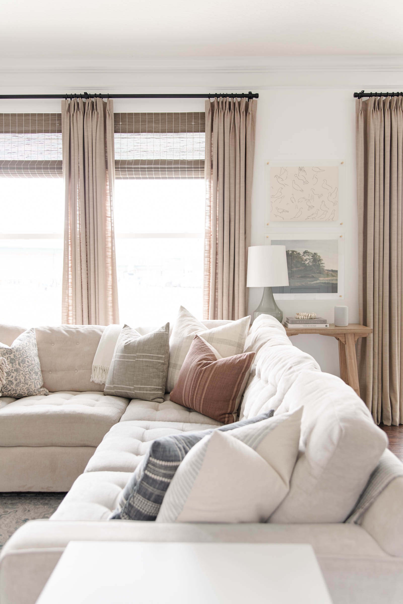 pinch pleat drapes paired with wood roman shades, cream sofa with throw pillows