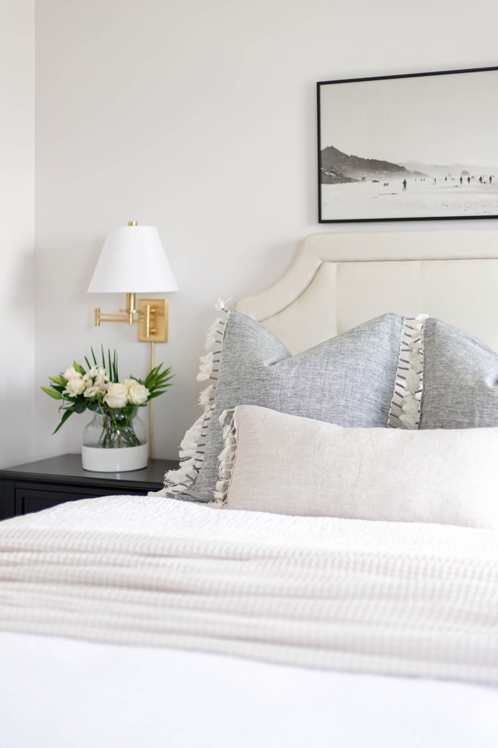 casual bedroom styling with white linen duvet and linen pillow covers, brass wall sconces