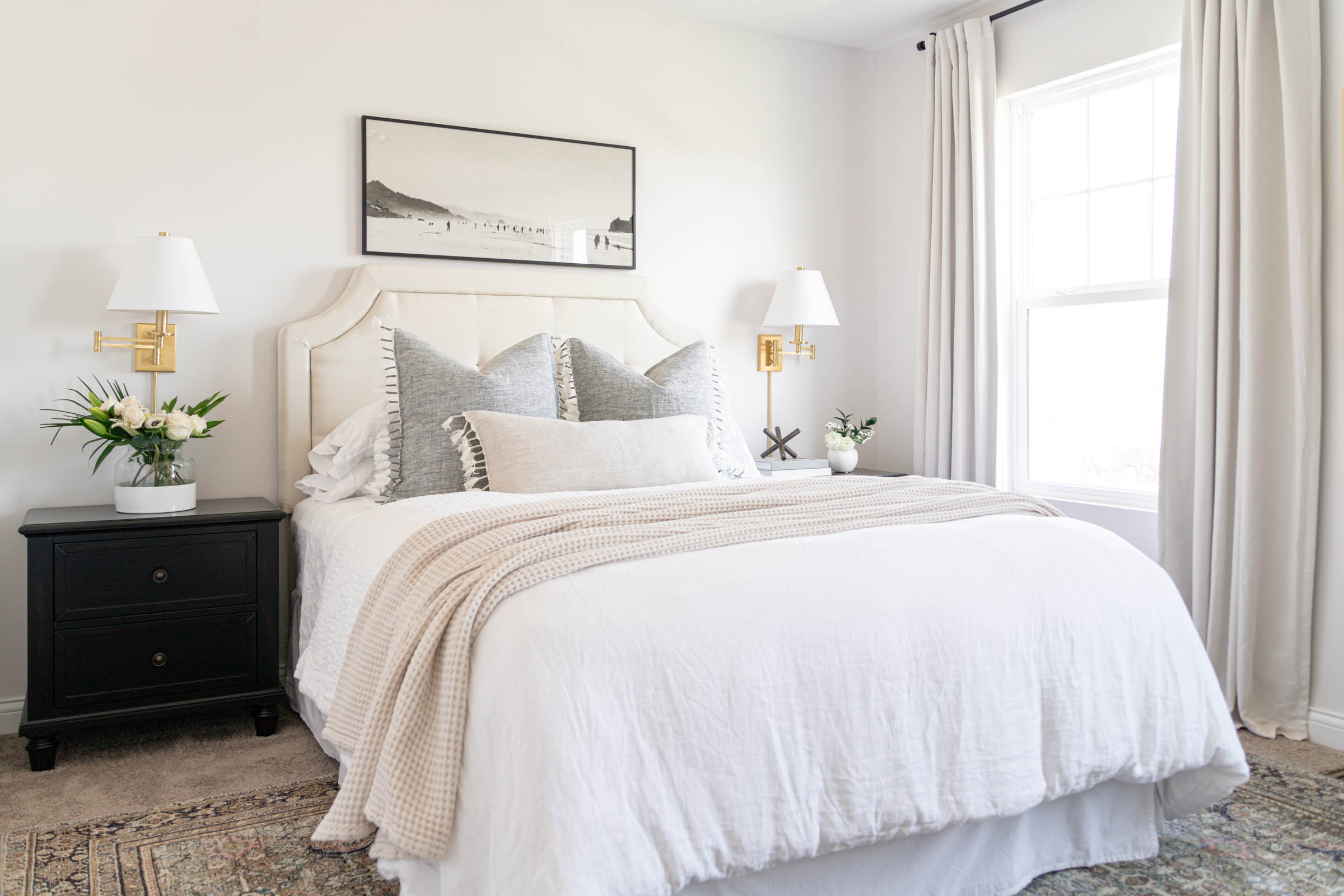 casual bedroom styling with white linen duvet, brass wall sconces