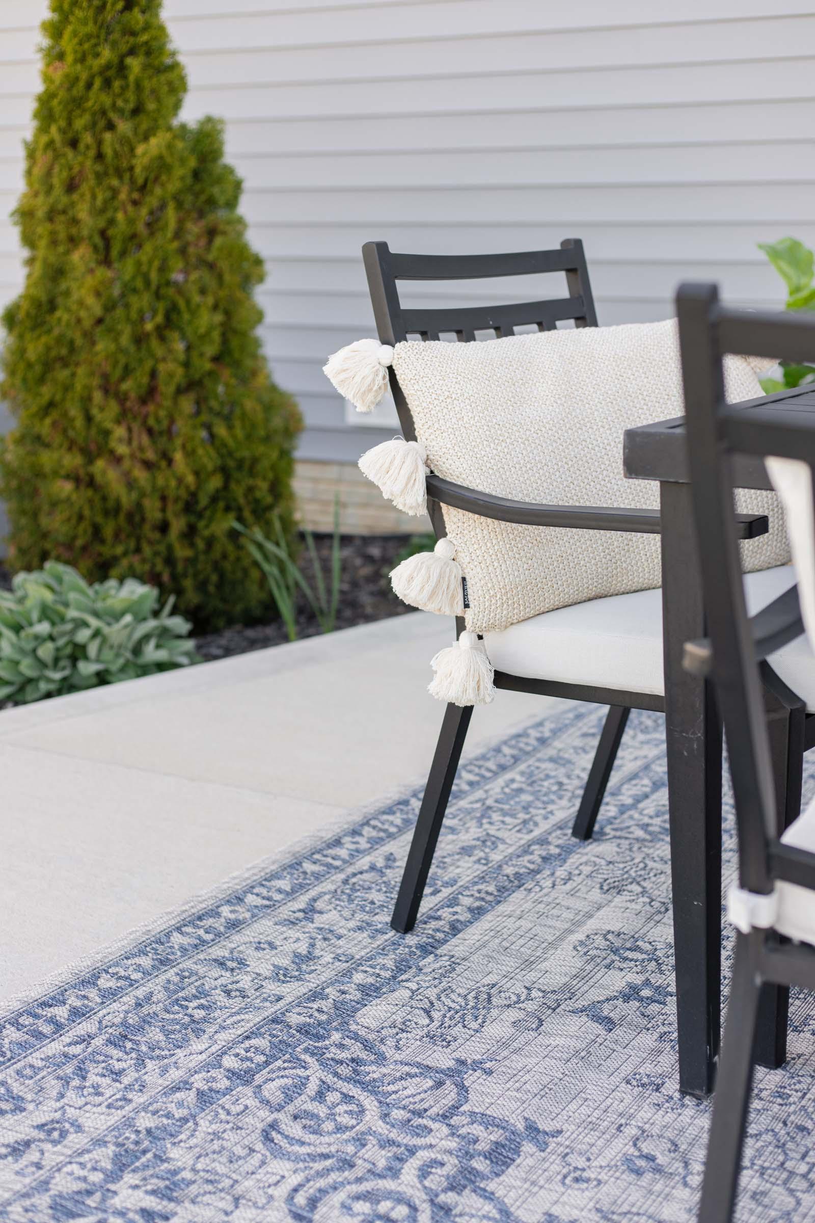 blue outdoor rug, black metal chair, lumbar pillow with tassels