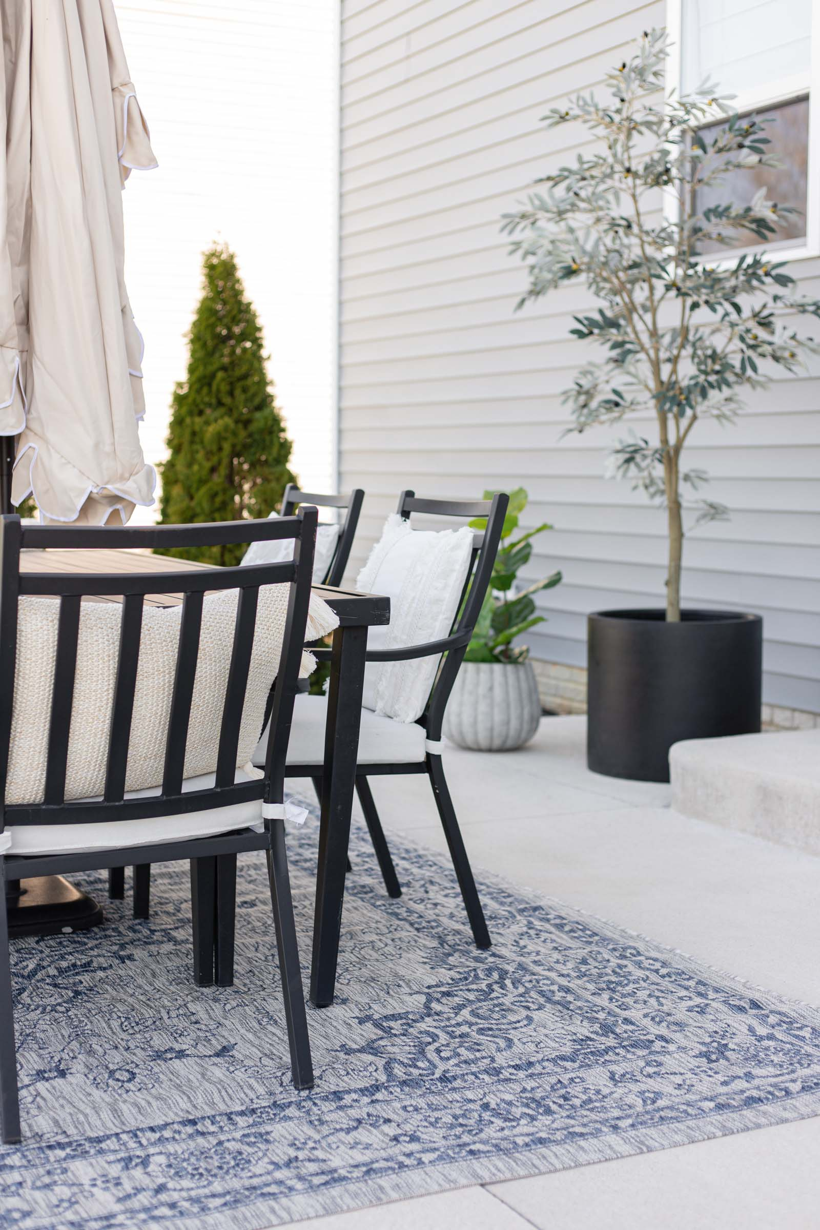 patio table with pillows and two planters with trees