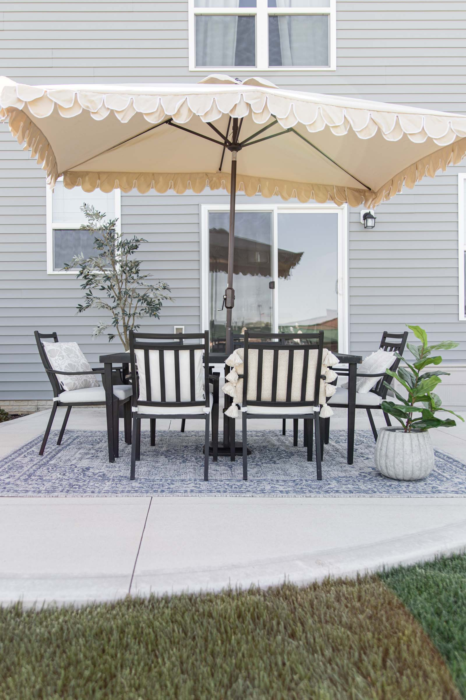 Simple Patio Decorating Ideas | beige umbrella with scalloped edge, blue outdoor rug, olive tree, pillows