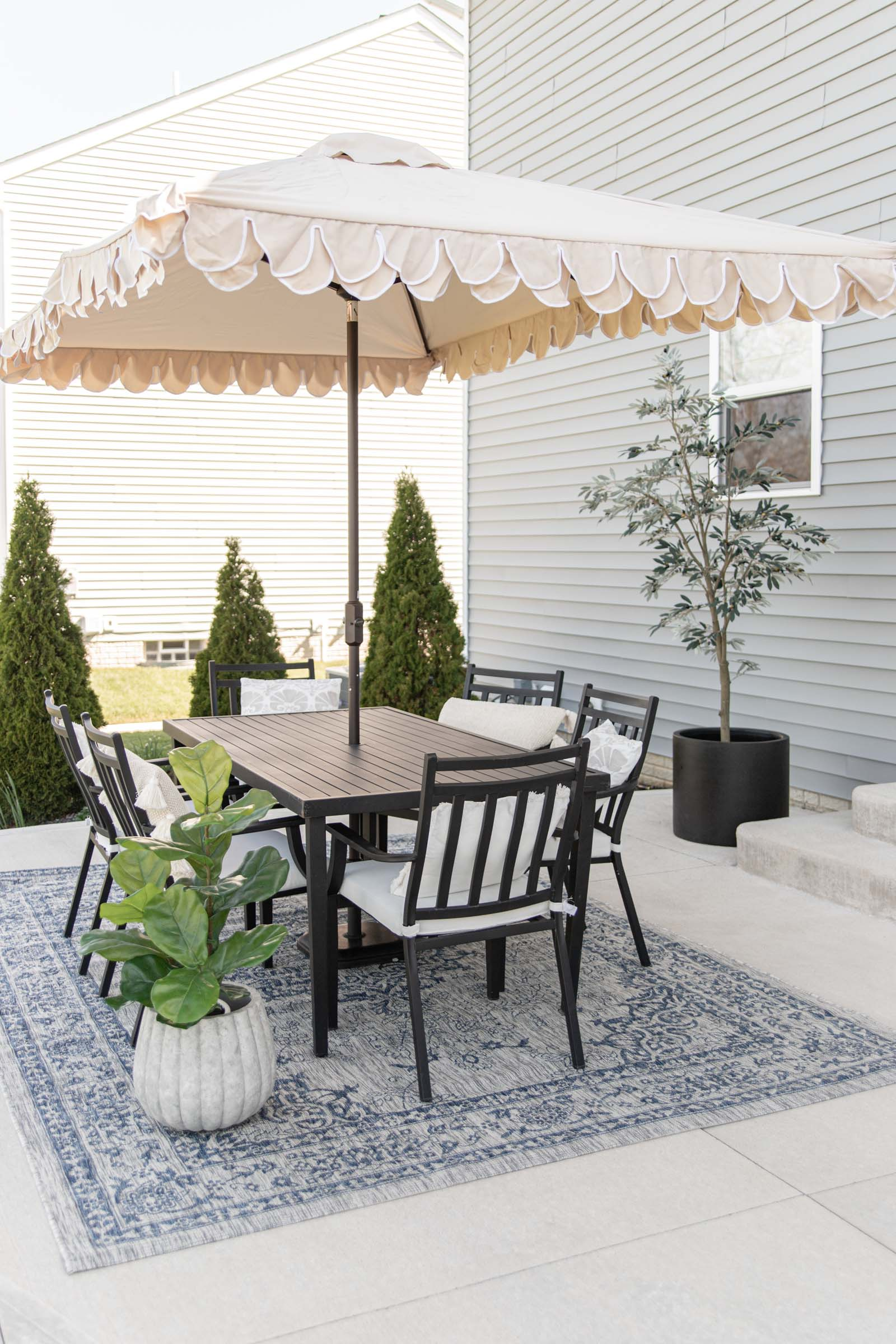 Simple Patio Decorating Ideas | beige umbrella with scalloped edge, blue outdoor rug, pillows