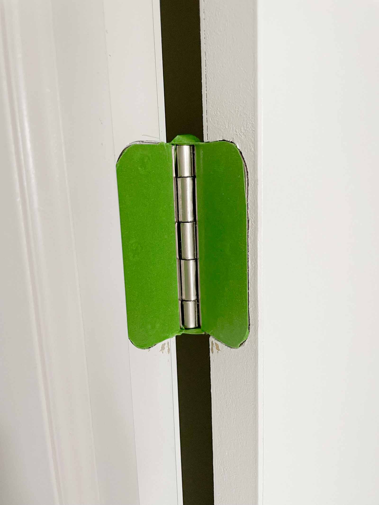 Painters tape covering door hinge, tips to paint interior doors