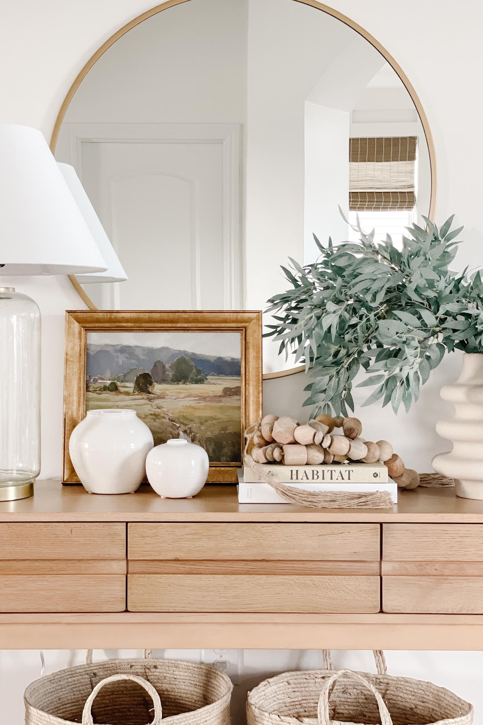 coastal entryway decor with Herriman wooden console table, framed landscape, brass lamp, wood bead garland, greenery in vase