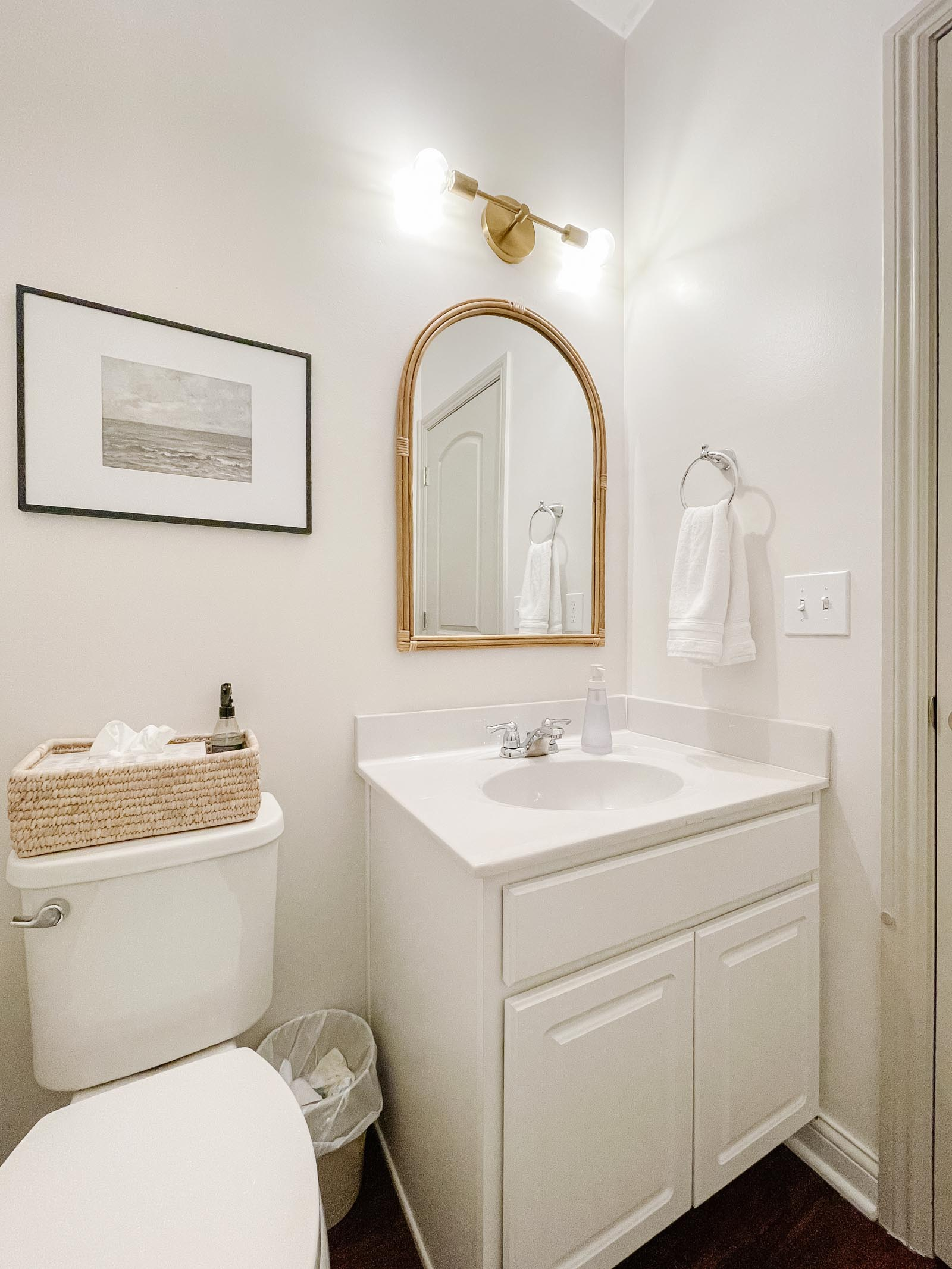 Powder Room Before - rattan arched wall mirror, modern brass light fixture, white cabinetry and toilet