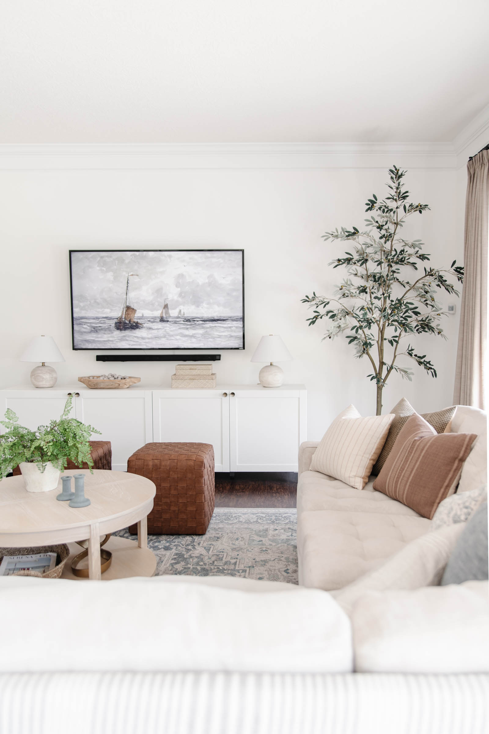 living room with wide white media console, artificial olive tree, mauve terracotta pillow cover, faux leather woven cubes