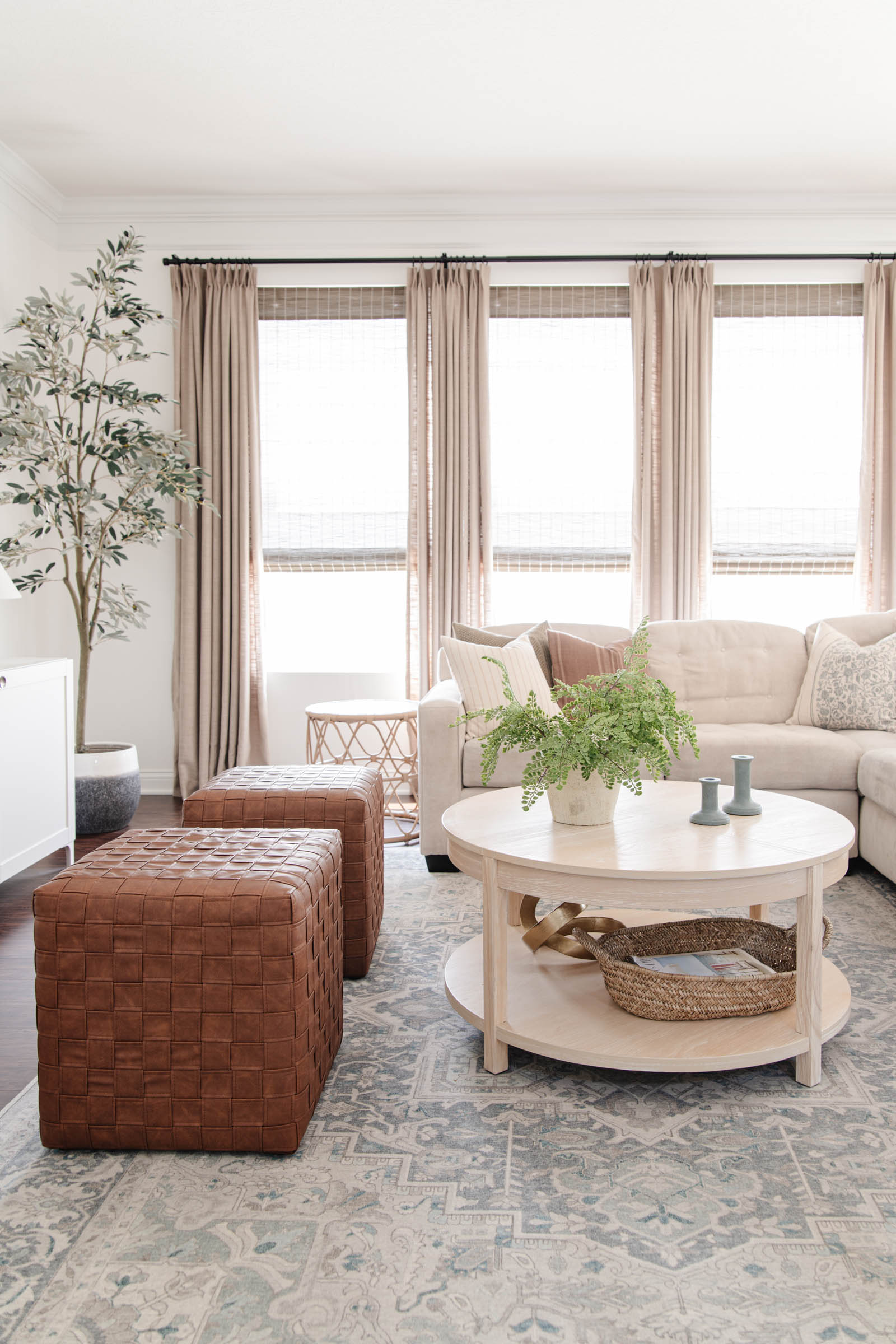 Modern traditional living room with blue vintage style rugs, faux leather woven cubes, grey beige twopages drapes