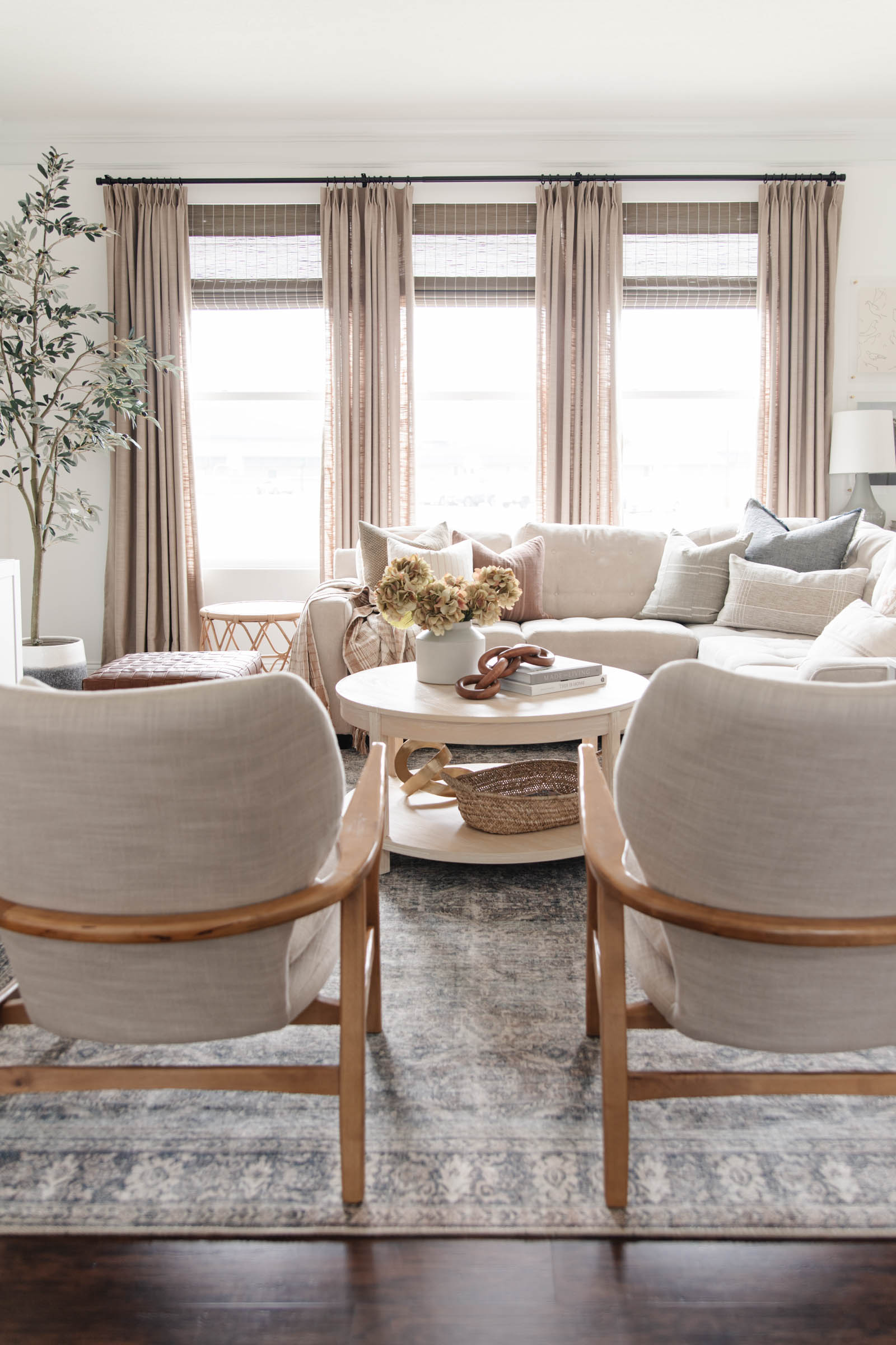 gray beige pinch pleat drapes from Amazon, affordable curtains, Loloi Wynter grey charcoal area rug, round wood coffee table, neutral living room