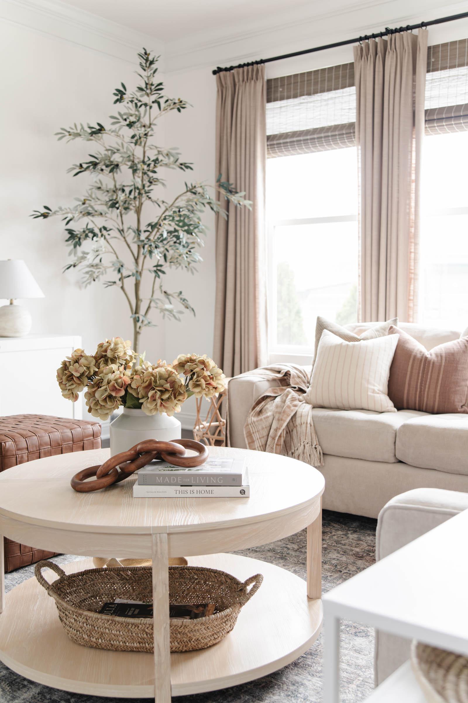 porto round whitewashed wood coffee table, Studio McGee decorative teak wood chain figurine, faux hydrangeas, mauve pillow, basket for magazines