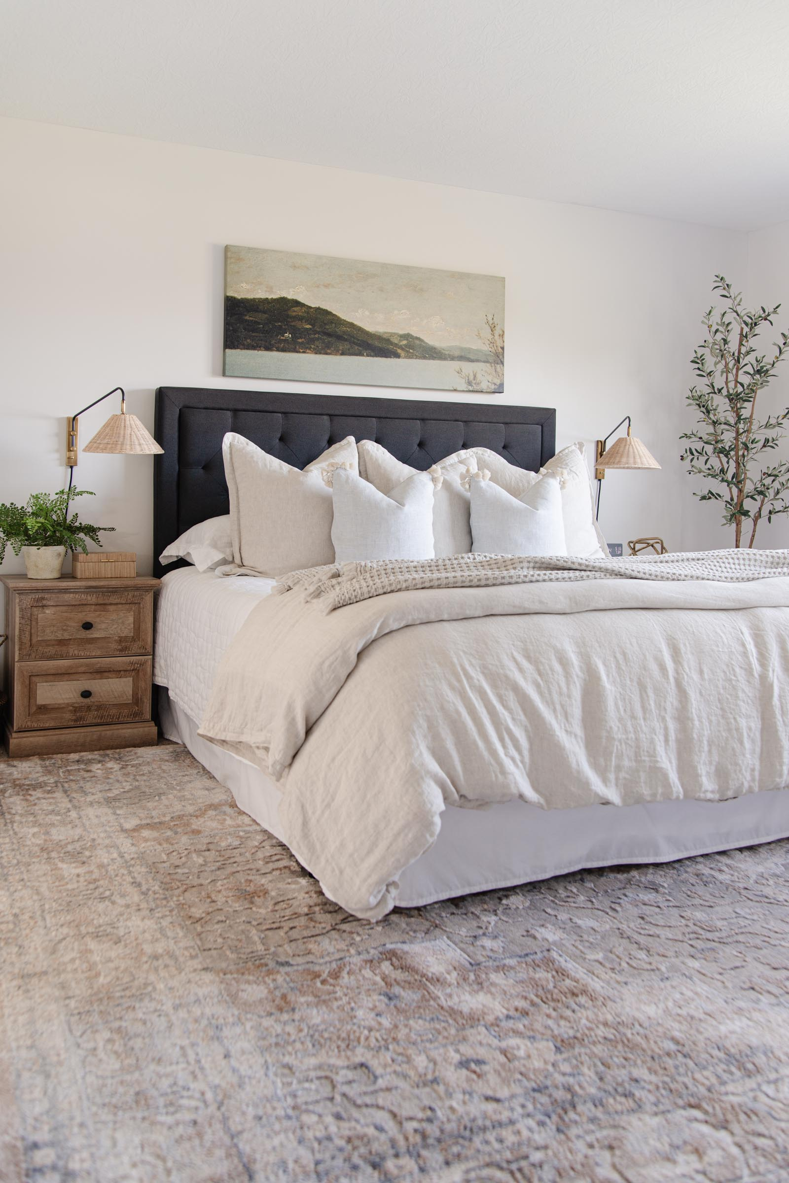 neutral bedroom with charcoal upholstered headboard, linen duvet cover, rattan wall sconces, faux olive tree, beige ivied medallion rug