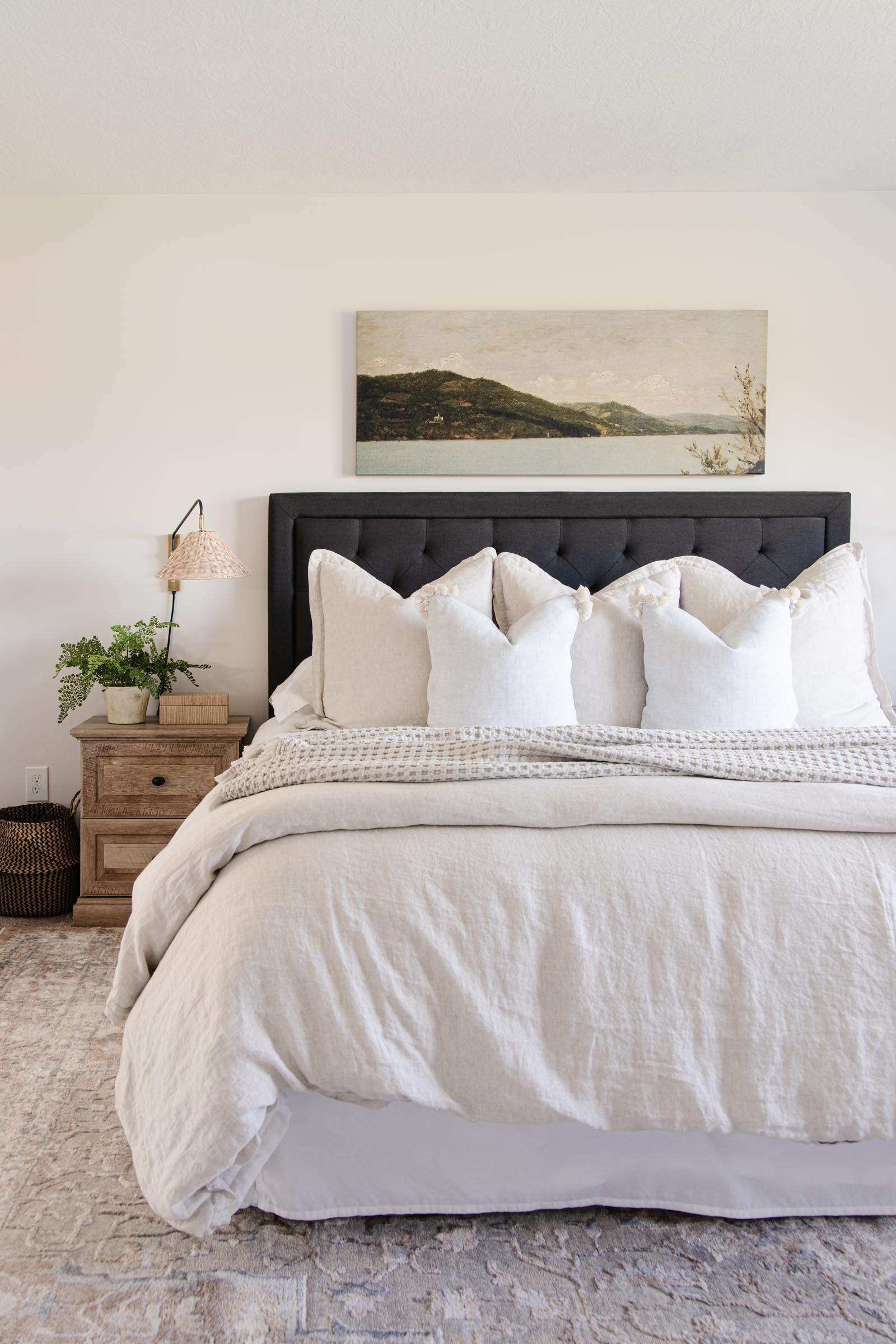 bedroom with beige linen duvet cover, long landscape painting, Flynn single wall sconce with wicker shade, beachcomber cotton throw
