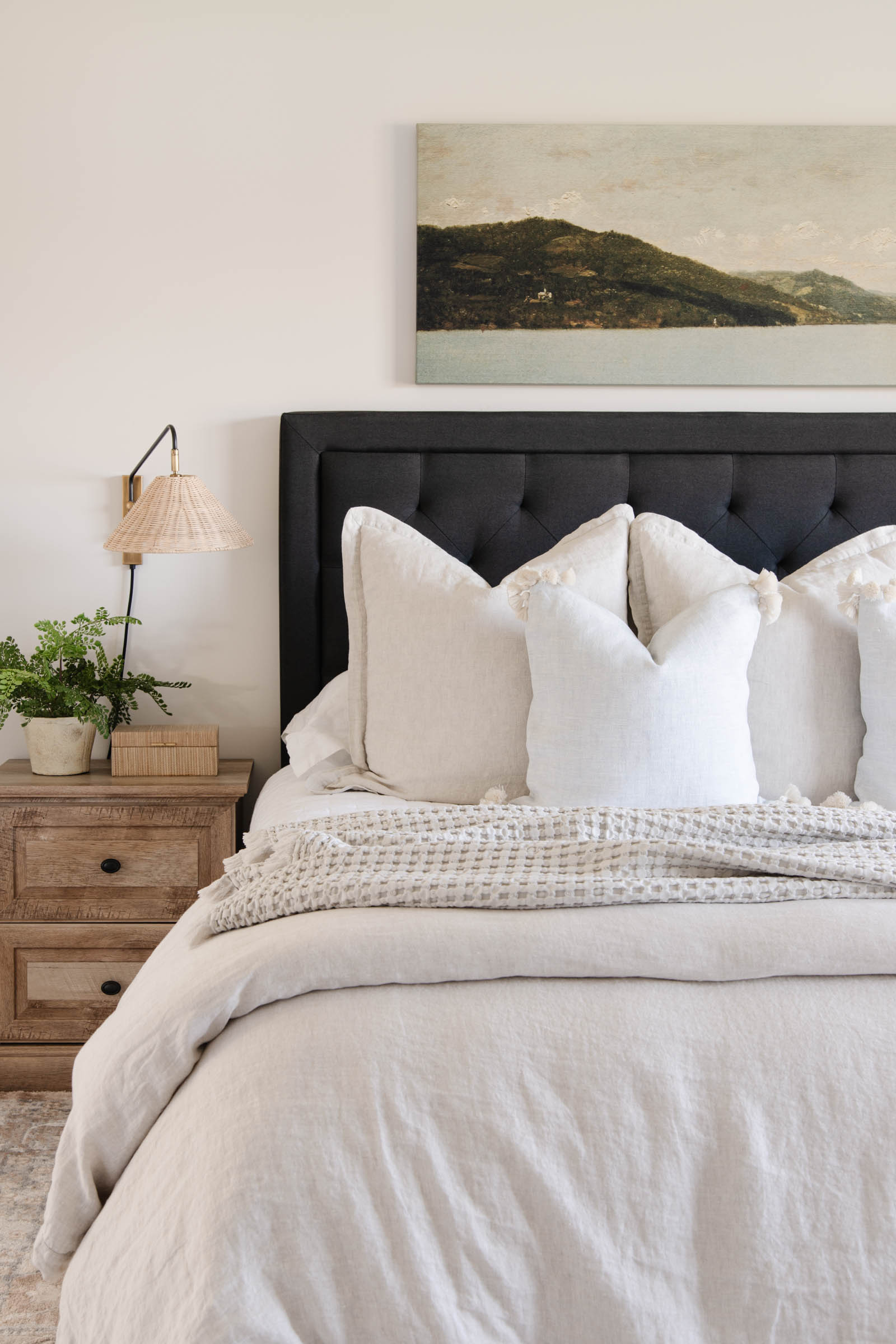 bedroom with beige linen duvet cover, long landscape painting, Flynn single wall sconce with wicker shade