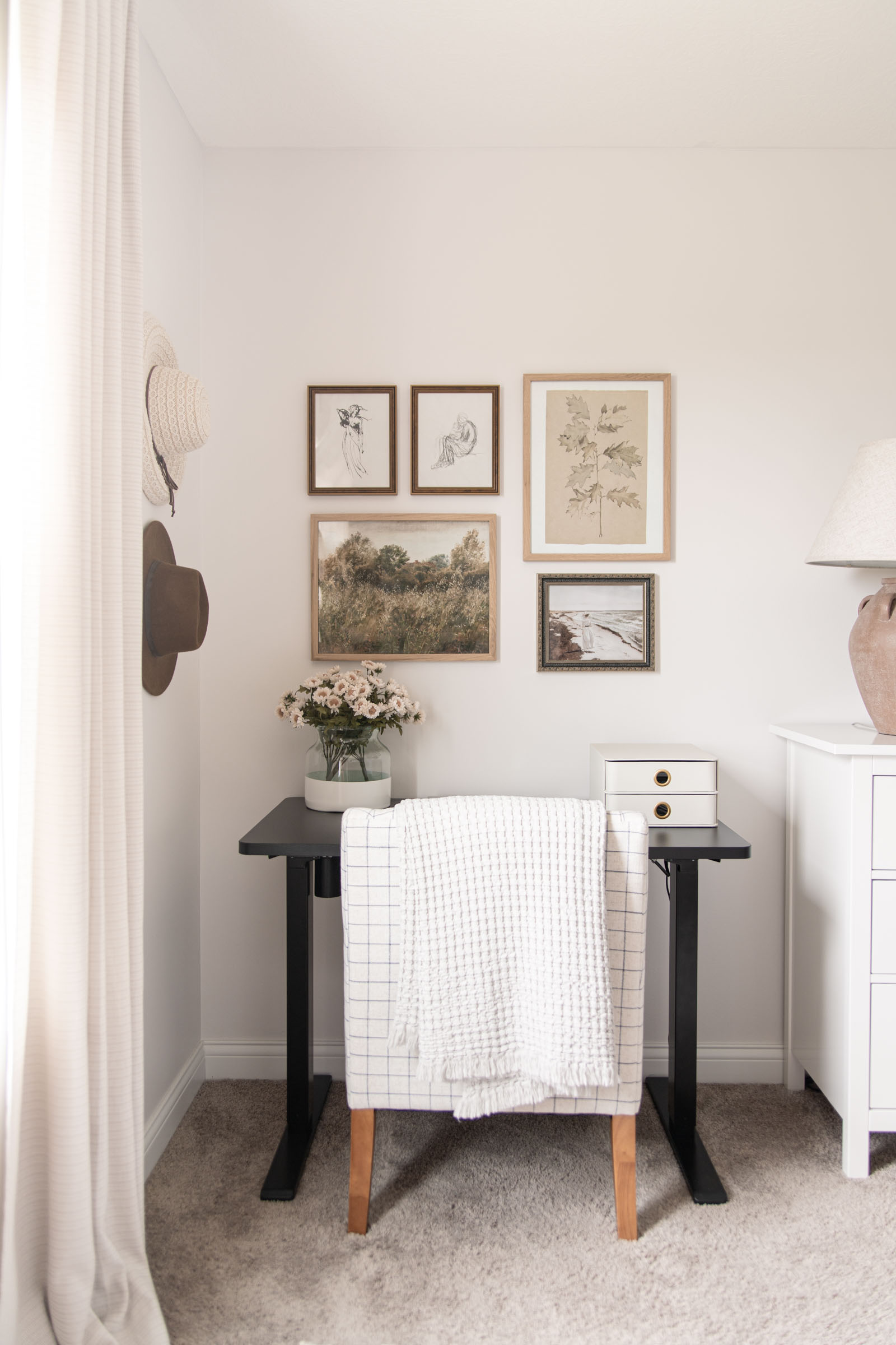 Bedroom Office Nook (and Vintage Art Gallery Wall) | black sit to stand electric standing desk, hats hanging on wall, poetto vase, collected antique art gallery wall, windowpane plaid chair