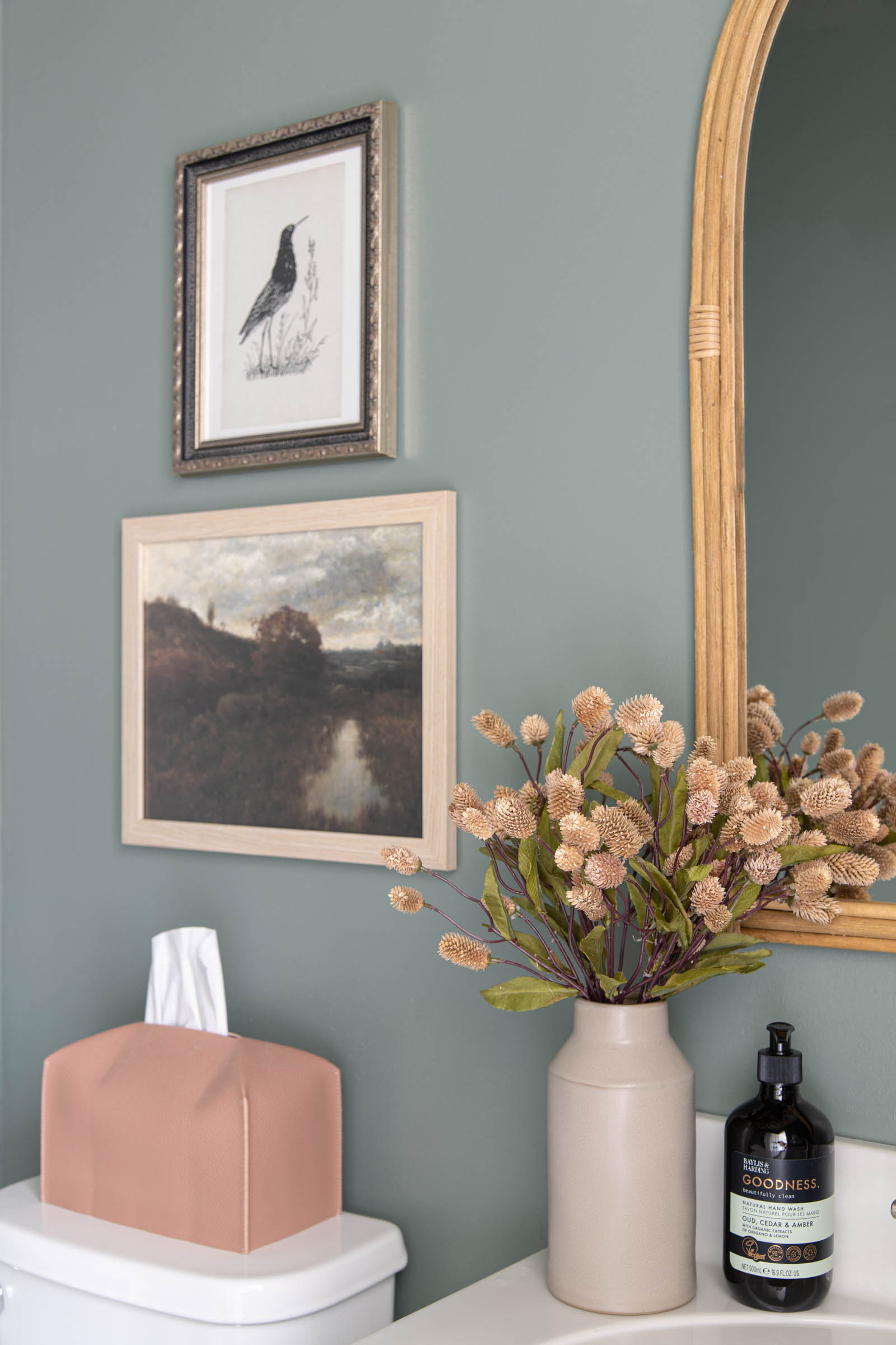 muted green wall paint, arched rattan mirror, vintage landscape art, leather tissue box cover, dried florals