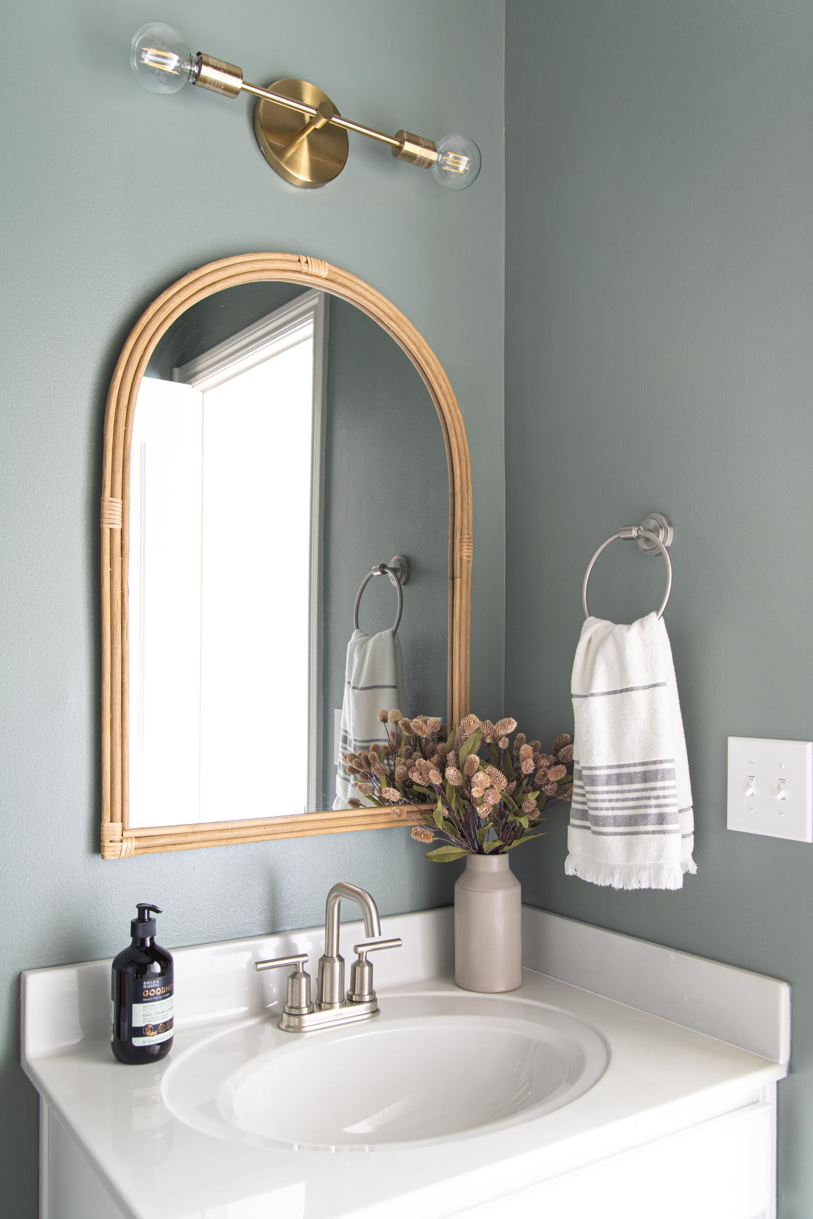 Budget Friendly Powder Room Reveal | muted green wall paint, arched rattan mirror, vintage landscape art, leather tissue box cover, dried florals, modern bathroom faucet