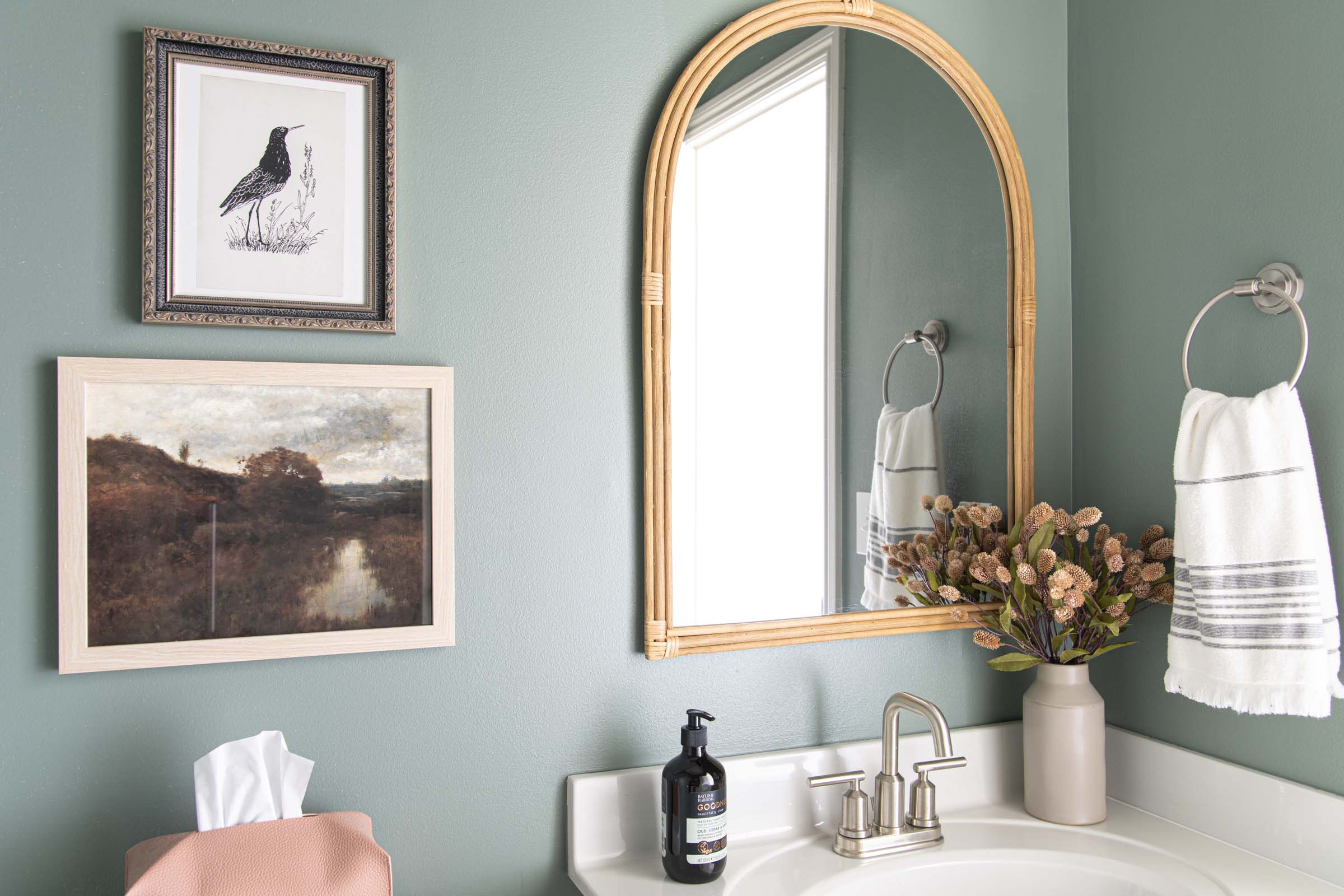 muted green wall paint, arched rattan mirror, vintage landscape art, leather tissue box cover, dried florals, modern bathroom faucet
