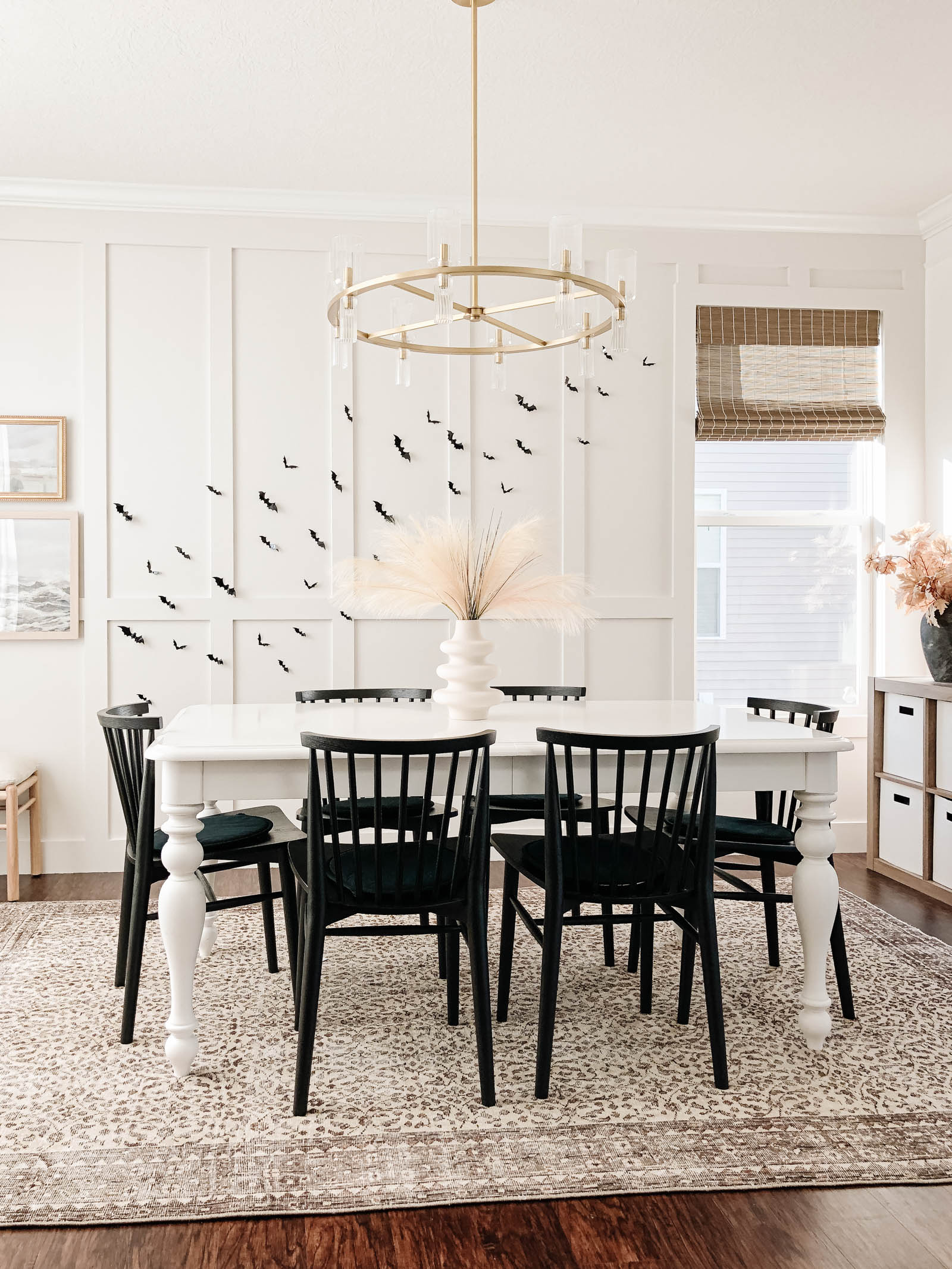 Bats on dining room wall, minimal and neutral Halloween decor, classy Halloween, brown vintage rug, black dining chairs