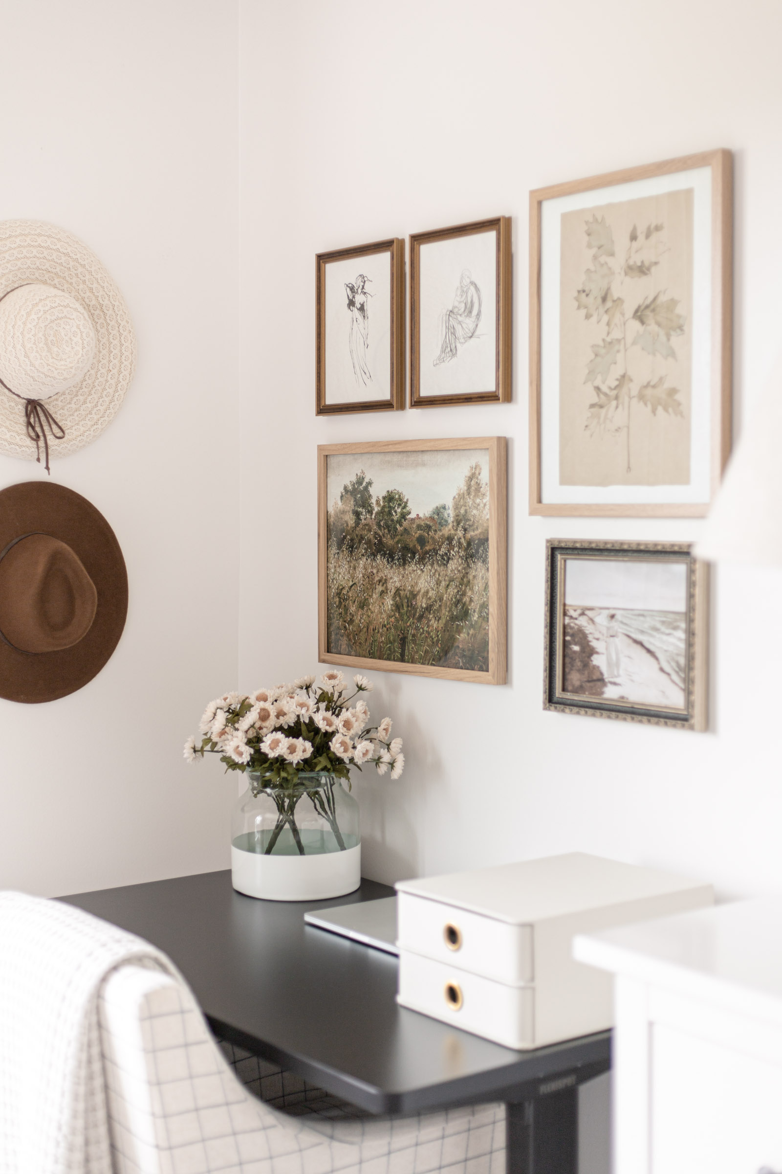 Bedroom Office Nook (and Vintage Art Gallery Wall) | black sit to stand electric standing desk, hats hanging on wall, poetto vase, collected antique art gallery wall