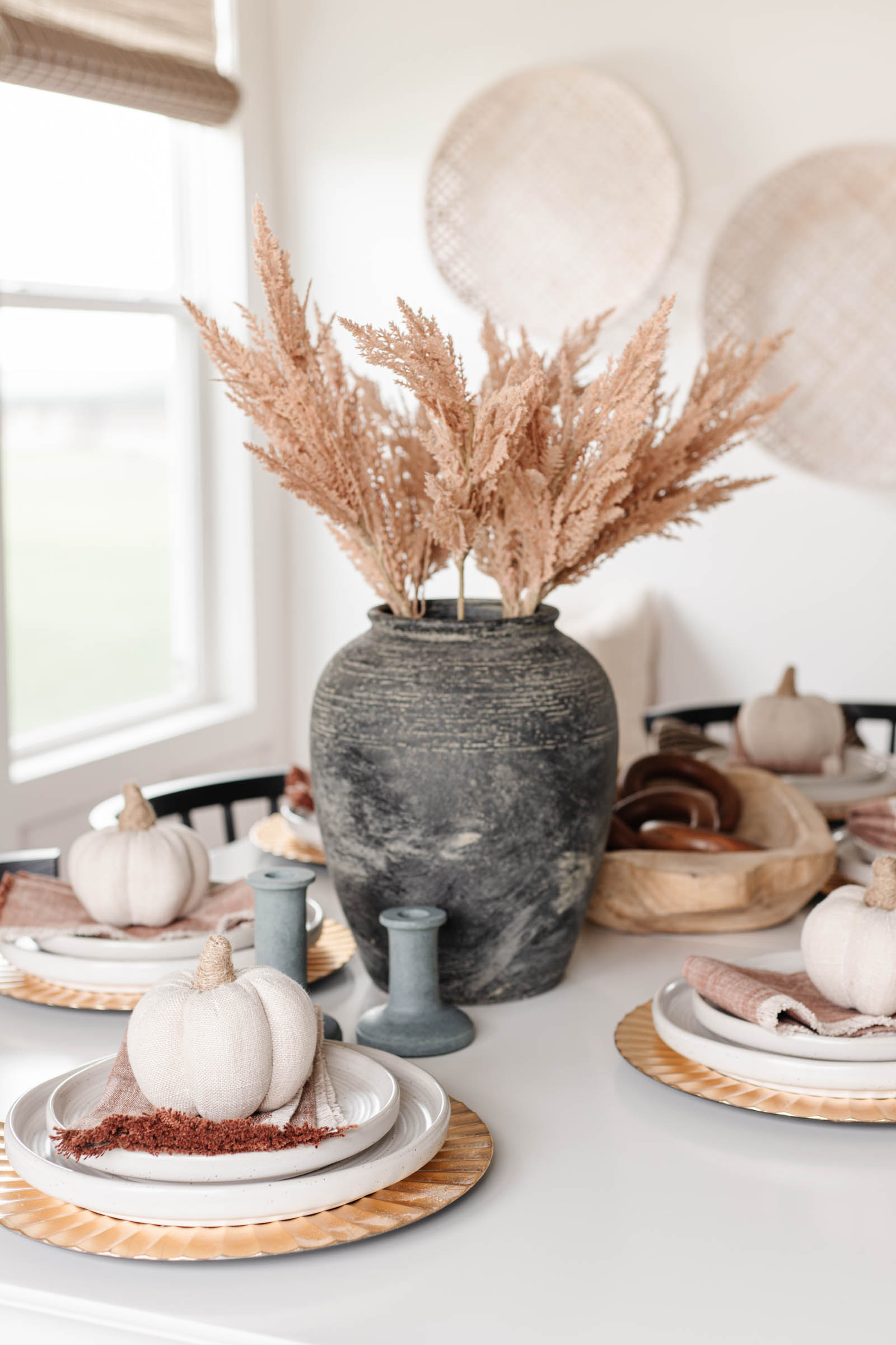faux pampas grass stems in black jar stone vase, cozy fall tablescape