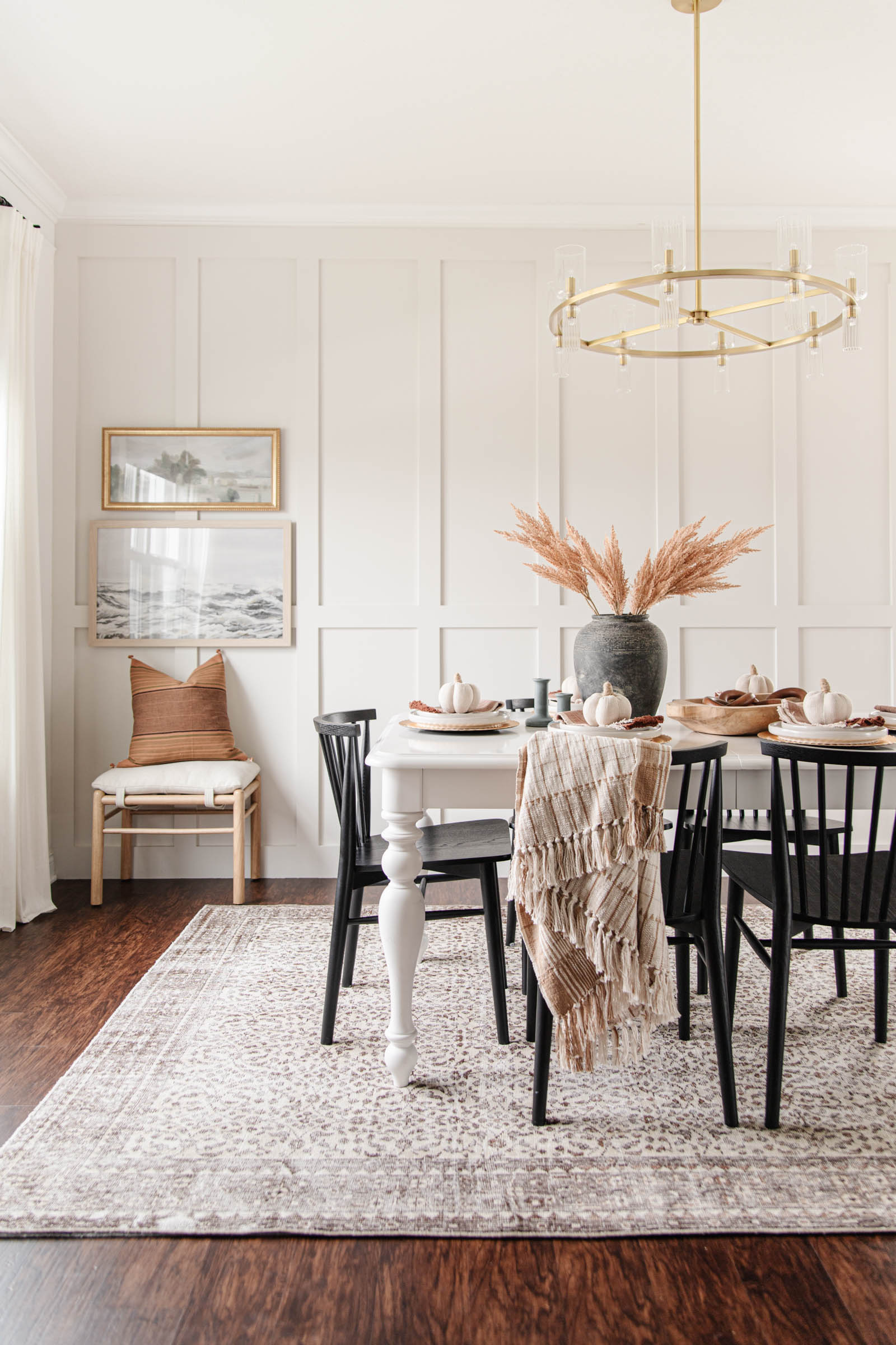 dining room with modern black dining chairs, fall tablescape, brass ring chandelier, white farmhouse table, wooden bowl, fabric pumpkins, brown vintage rug