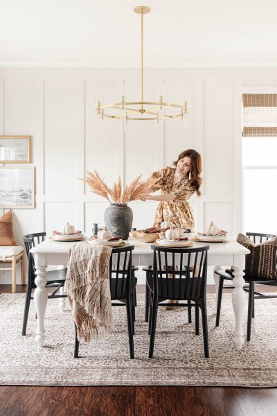 Cozy Fall Tablescape for Autumn Entertaining | muted fall colors, earth tones, faux pampas grass in black jar vase, vintage brown rug, brass chandelier, table decor with linen pumpkins