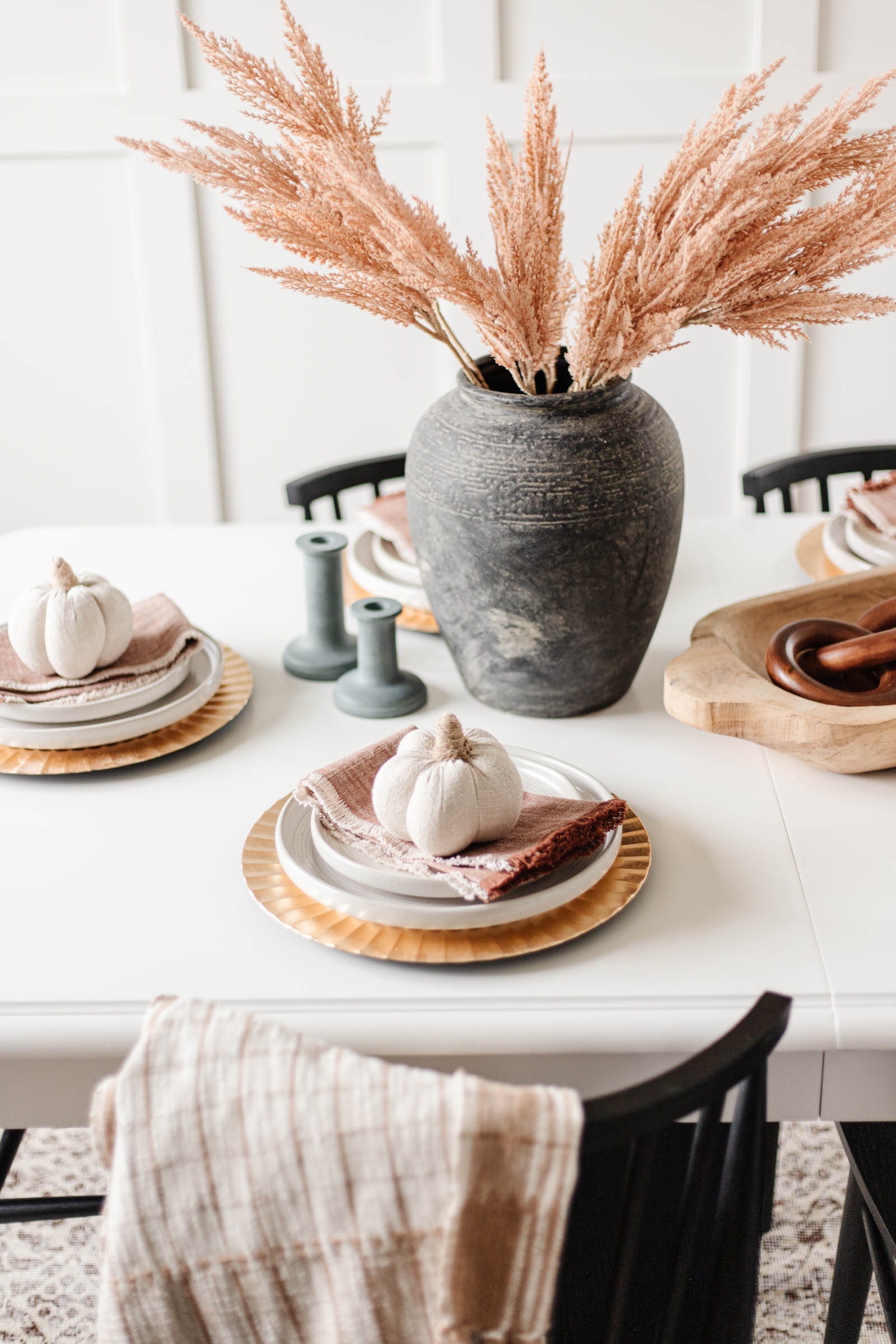 place setting with gold fluted charger, stoneware plates, rust cloth napkin, and neutral fabric pumpkins