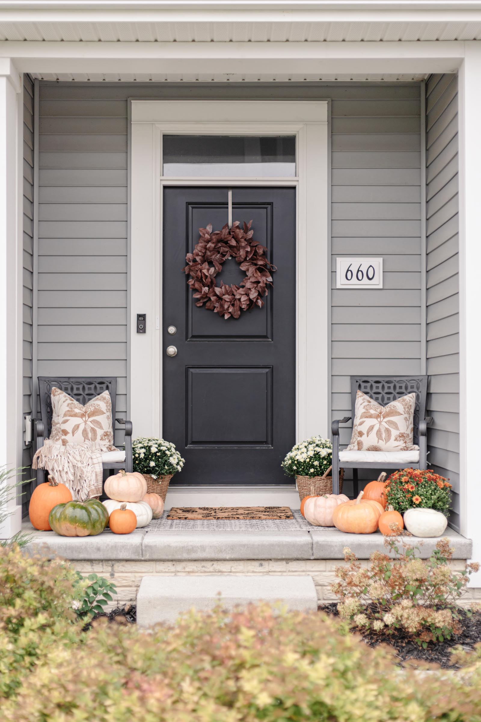fall front porch decor with autumn wreath, colorful pumpkins, fall pillows, outdoor chairs, layered rugs