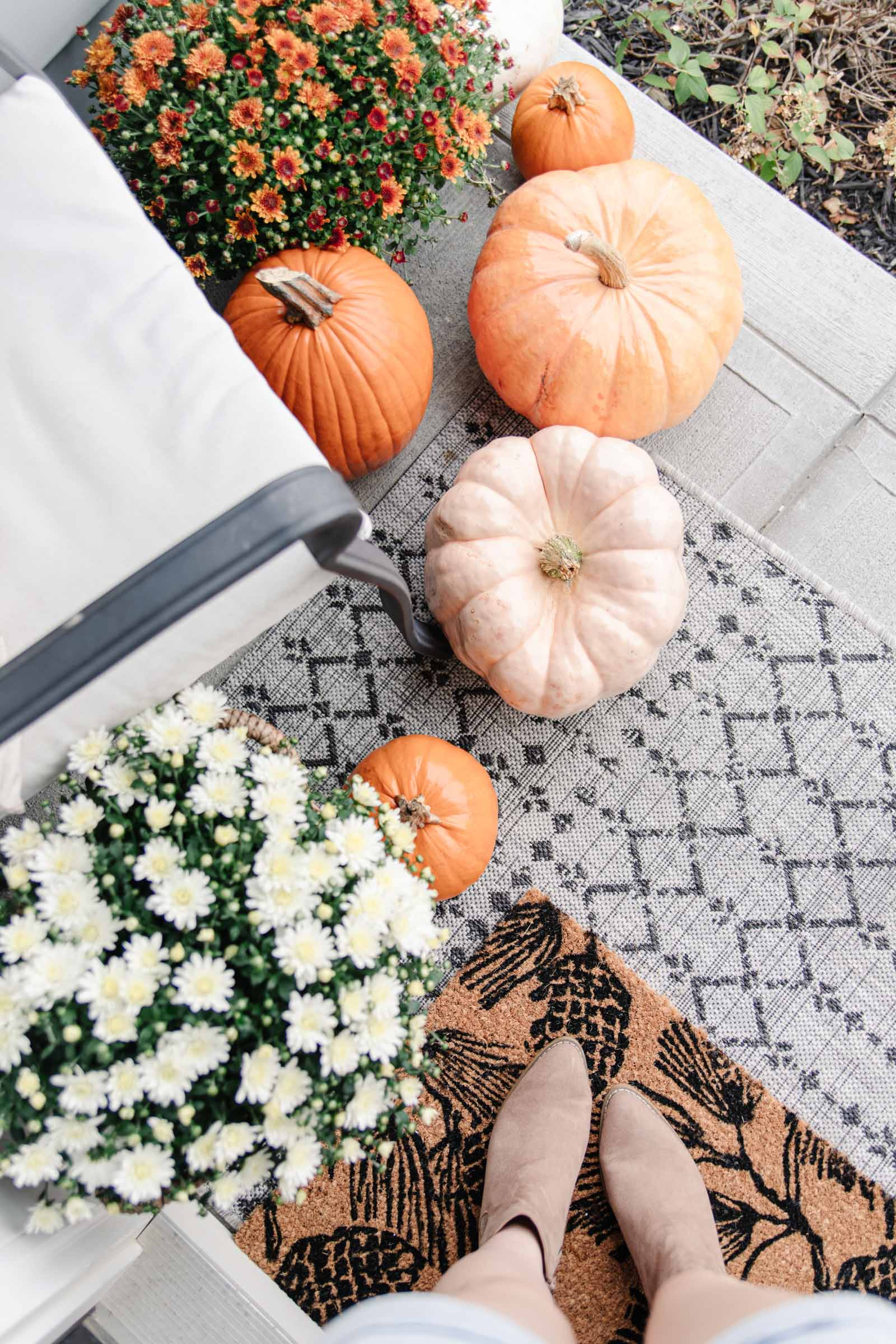 orange and pink pumpkins on front porch with white mum, suede boots